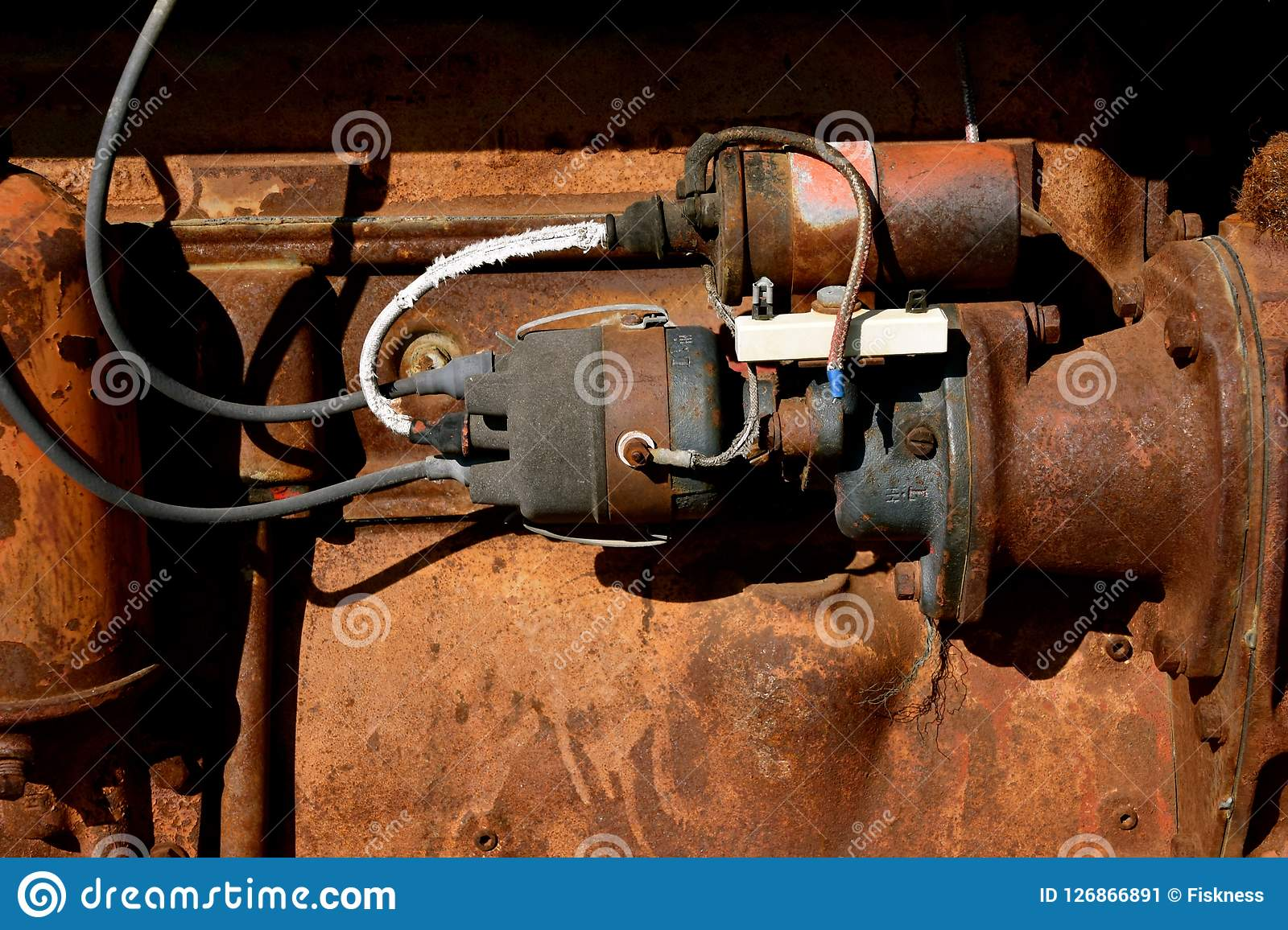 the electrical wiring and headquarters for starting an old rusty tractor