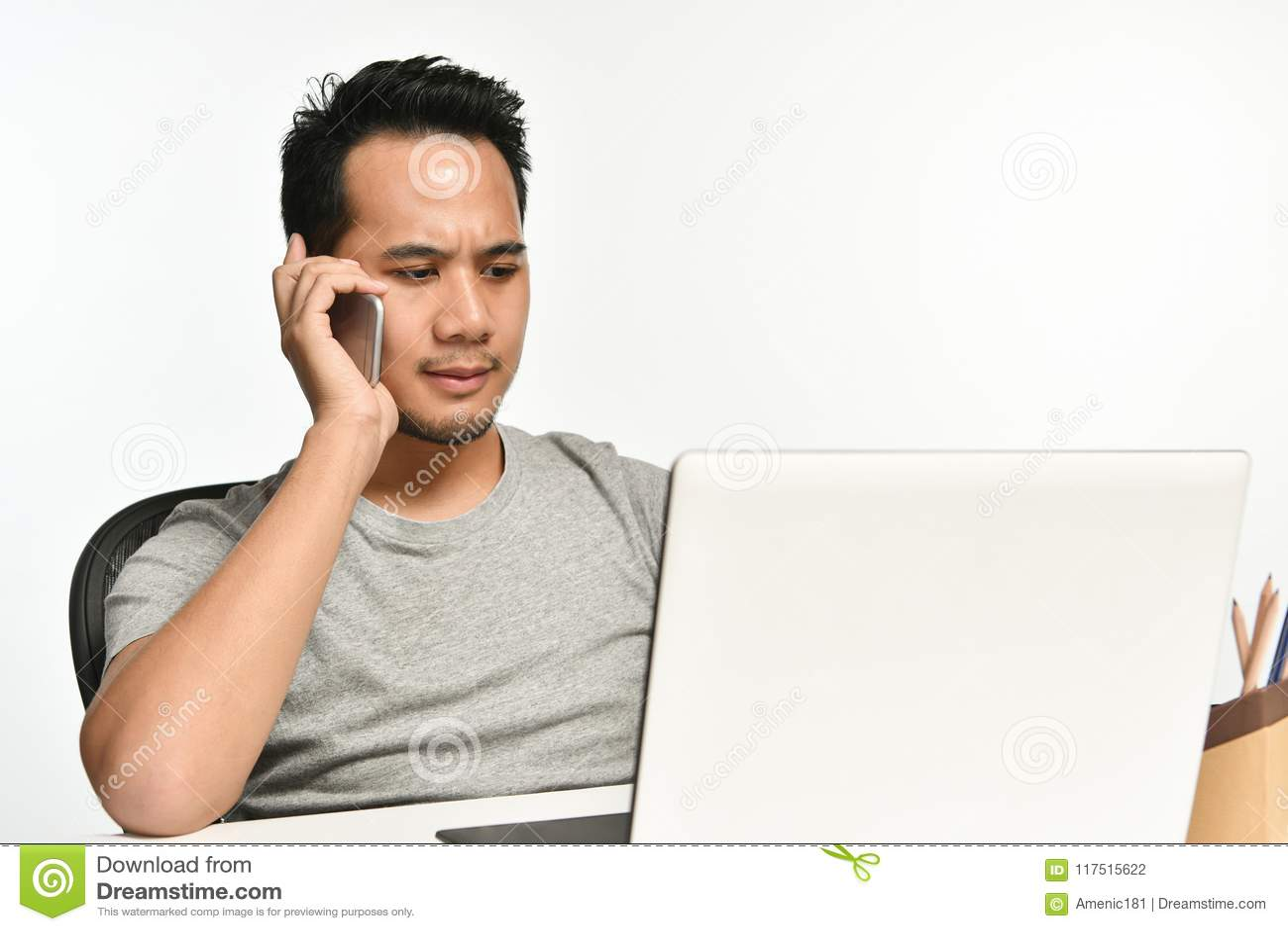 Startup affärsman som talar på telefonen och använder bärbara datorn