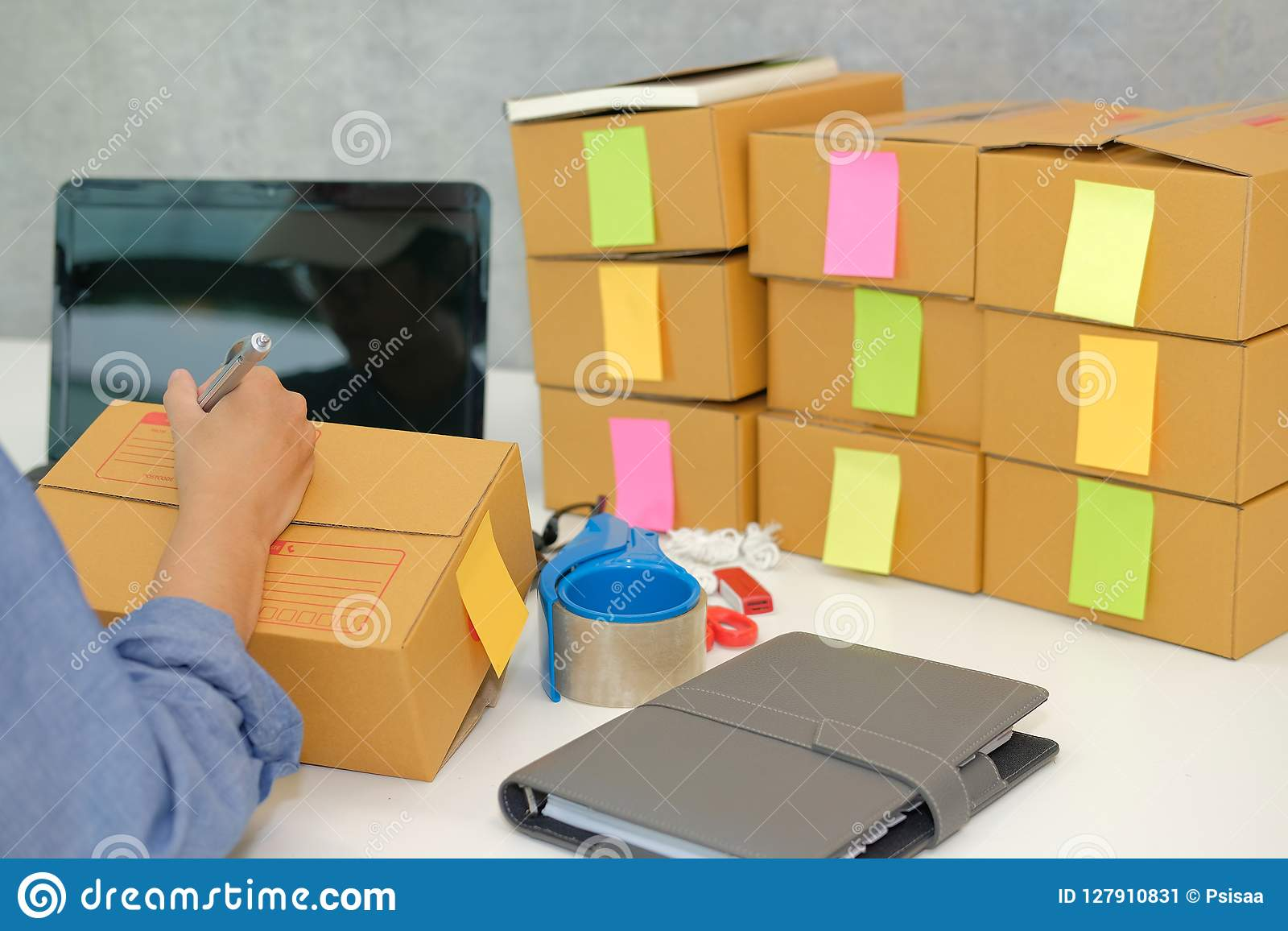startup business owner writing address on cardboard box. woman s