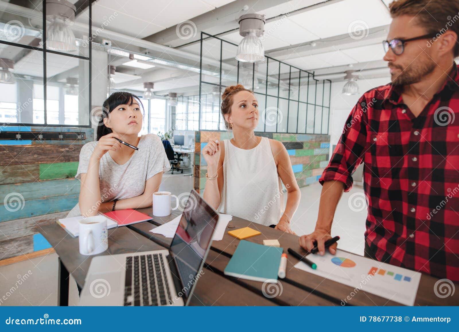 Startup möte runt om en tabell i modernt kontor