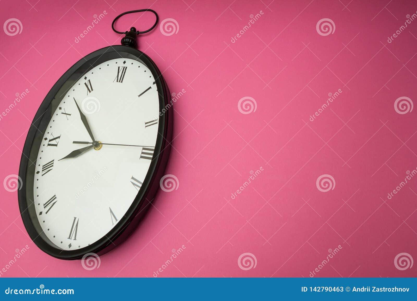 Stary ścienny zegar na różowym tle