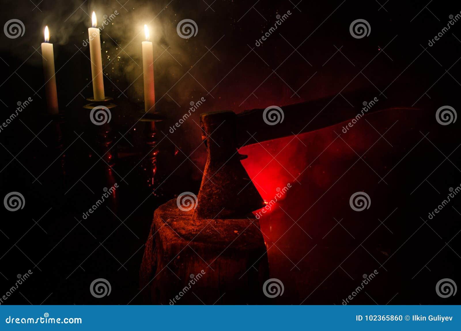 Stary ax dołączający drzewny bagażnik na horroru czerwonym mgłowym tle Straszny Halloweenowy temat z maniacką zabójca bronią