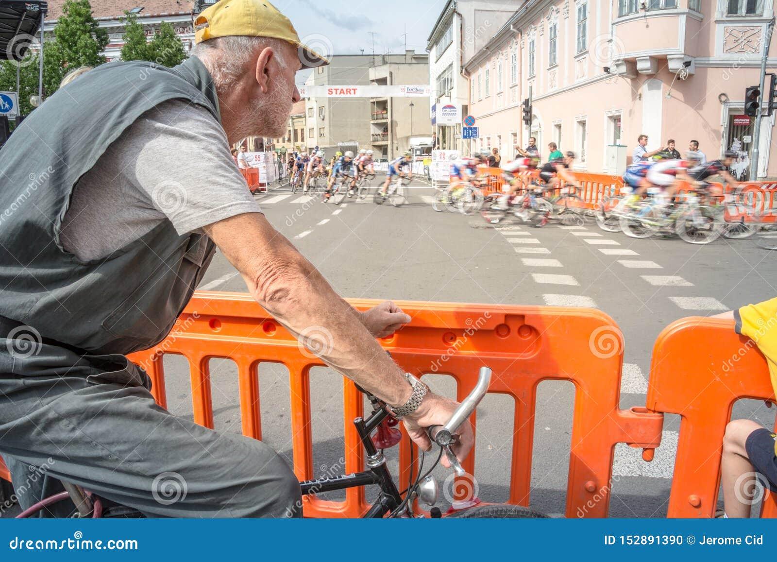 Stary człowiek, amatorski cyklista, obserwuje fachowych cyclistes z ich biegowym rowerowym omijaniem obok przed on z prędkości pl