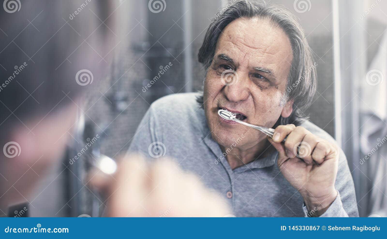Stary człowiek szczotkuje zęby przed lustrem