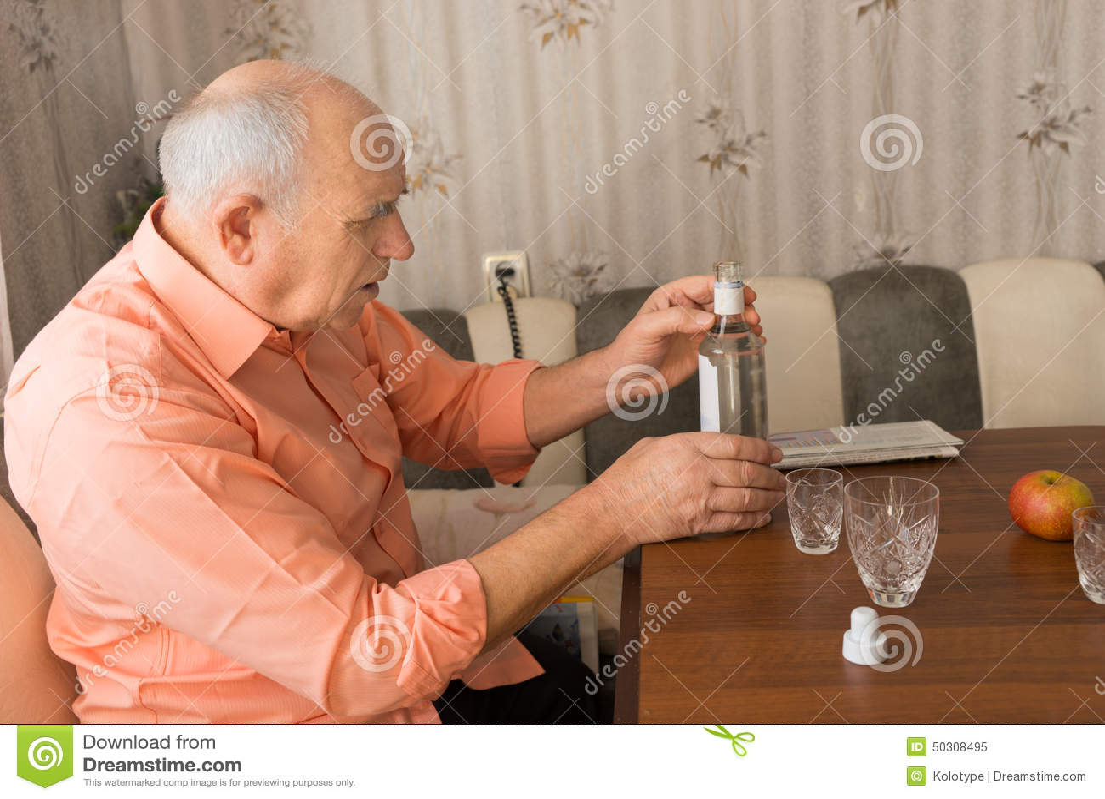 Stary Człowiek Trzyma butelkę wino na stole