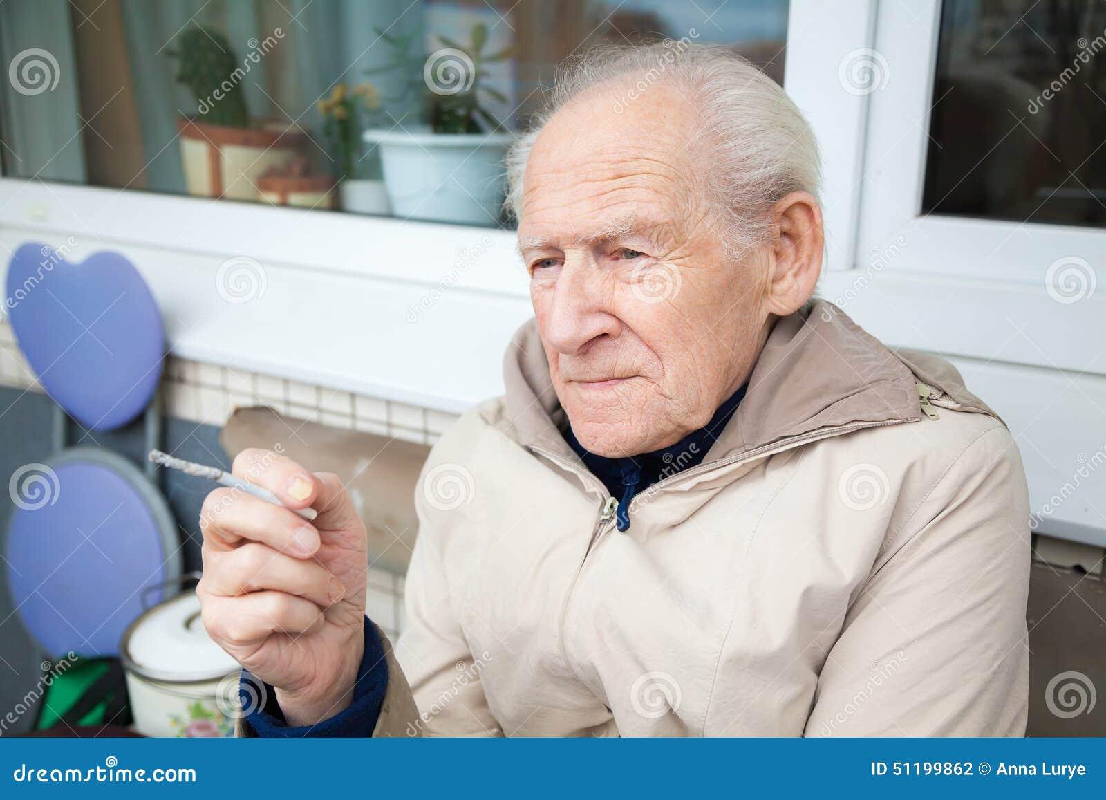 Stary człowiek trzyma papieros
