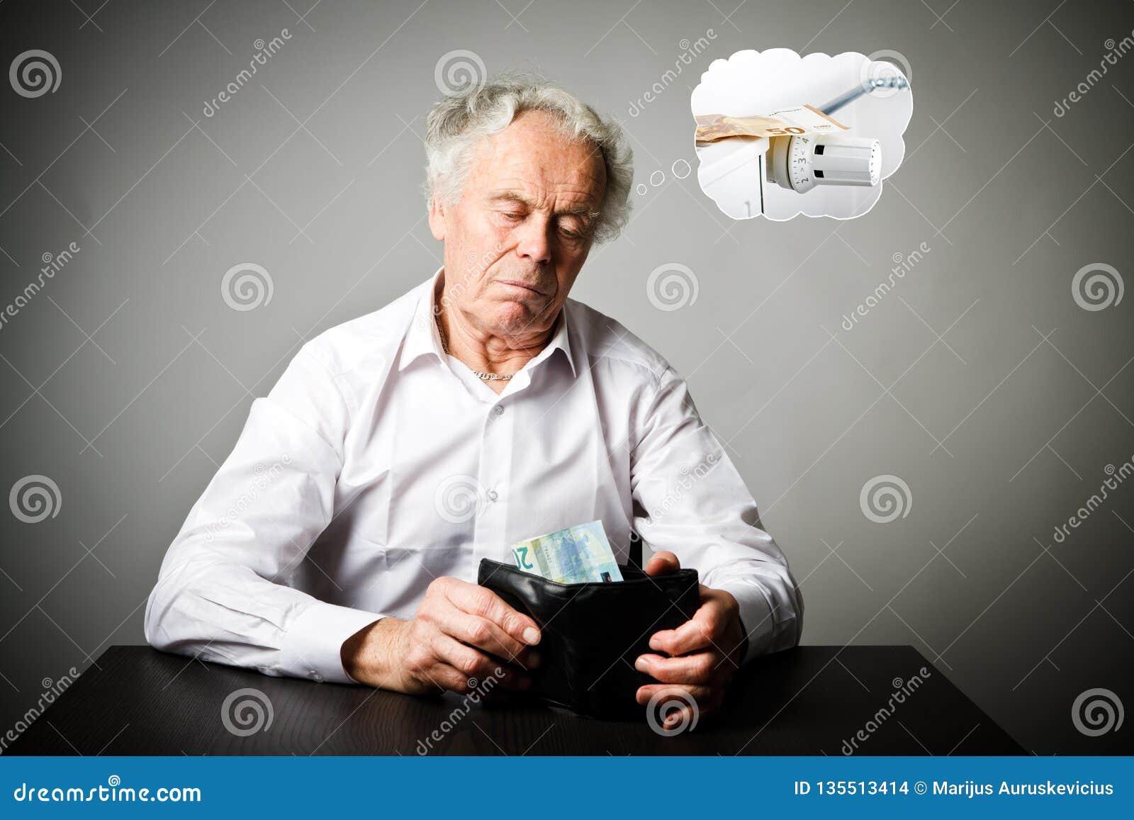 Stary człowiek w bielu i portfel z dwadzieścia euro Grzejny sezon, podatki i oszczędzania pojęcie, grzejnik
