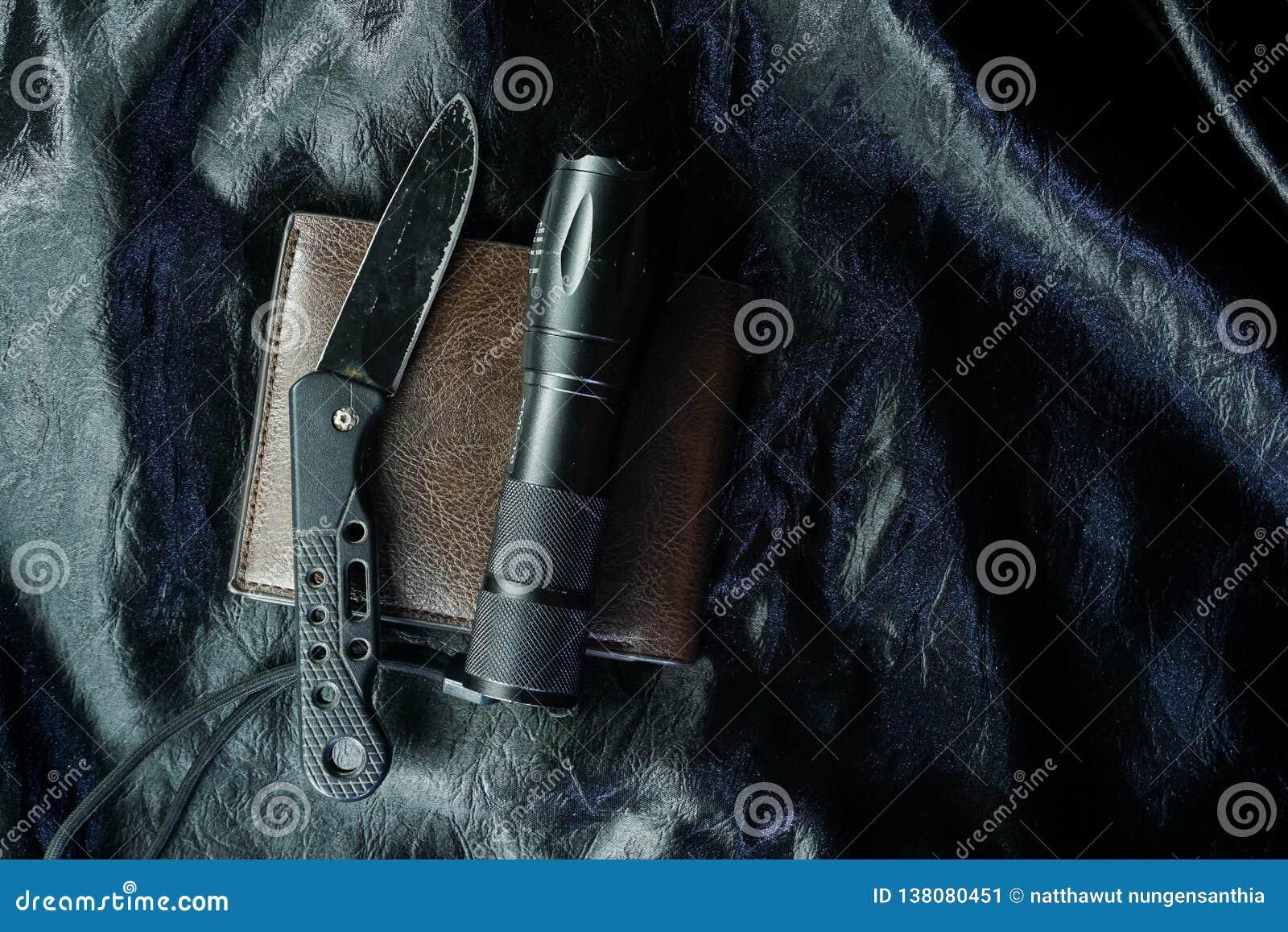 Stary czarny falcowanie nóż na czarnej tkaninie jest błyszczący
