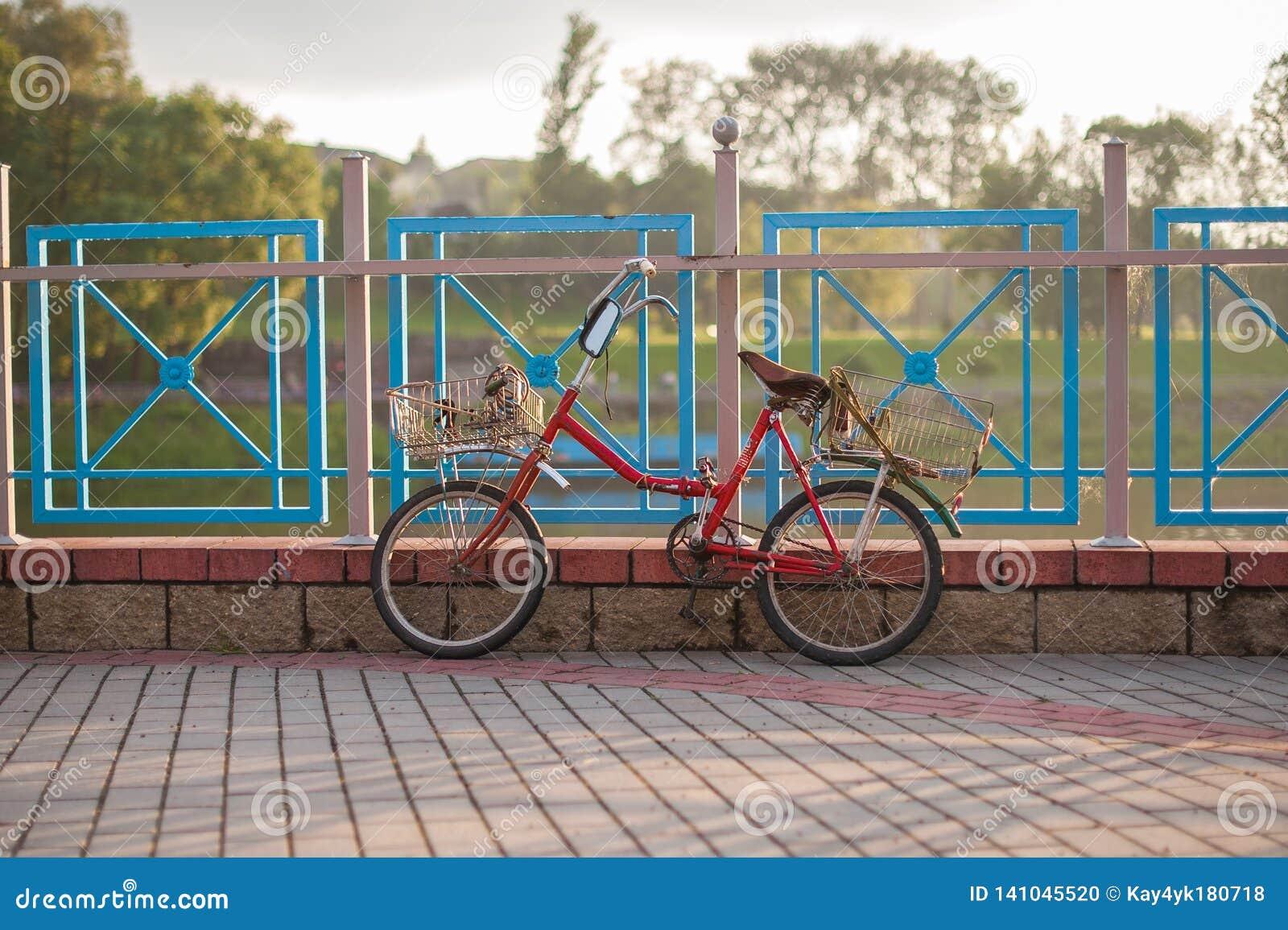 Stary czerwony bicykl z koszy stojakami na ogrodzeniu przy zmierzchem