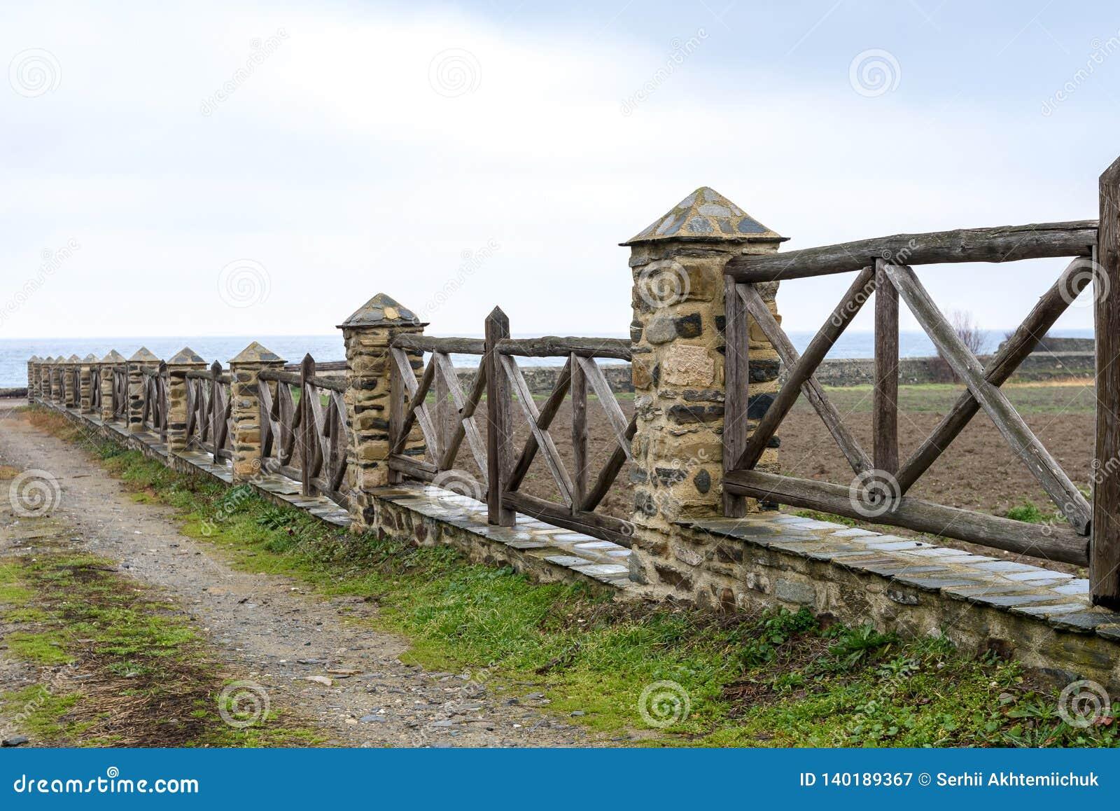 Stary drewniany ogrodzenie z ceglanymi kolumnami