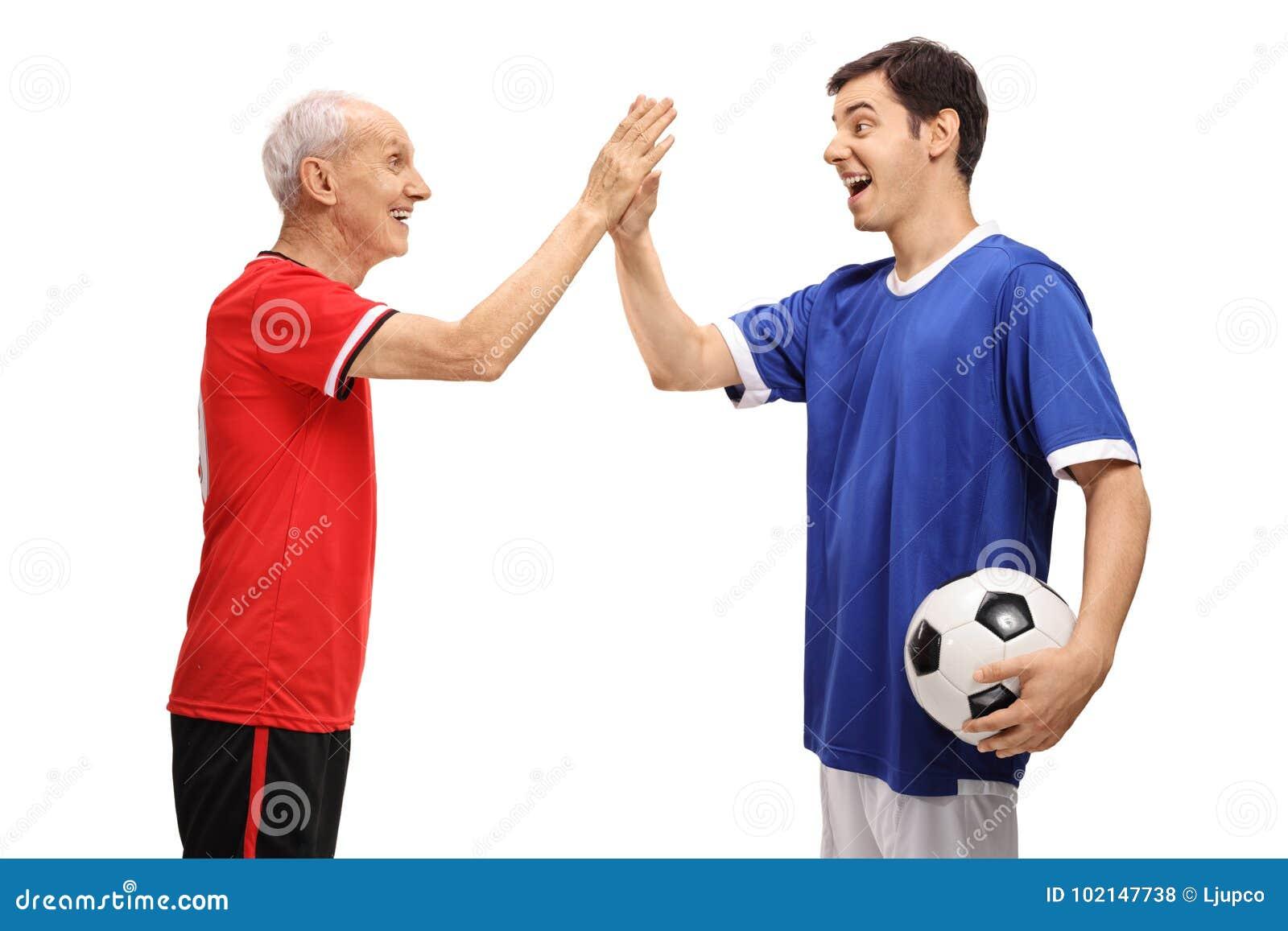 Stary futbolista i młodego futbolisty wysoki fiving