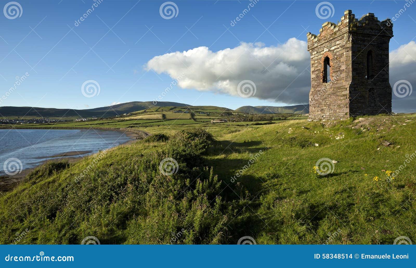 Stary kamienny zegarka wierza nad przyglądającą Dingle zatoką Co Kerry Irlandia jako łódź rybacka przewodzi out morze
