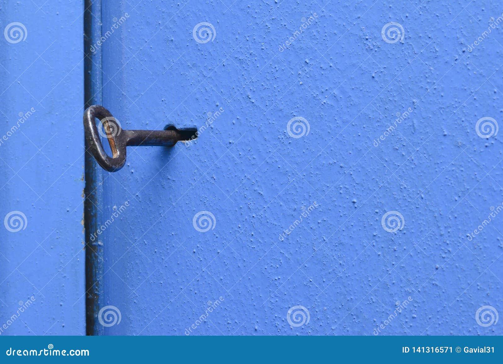 Stary klucz w keyhole Błękit, metalu drzwi z textured powierzchnią