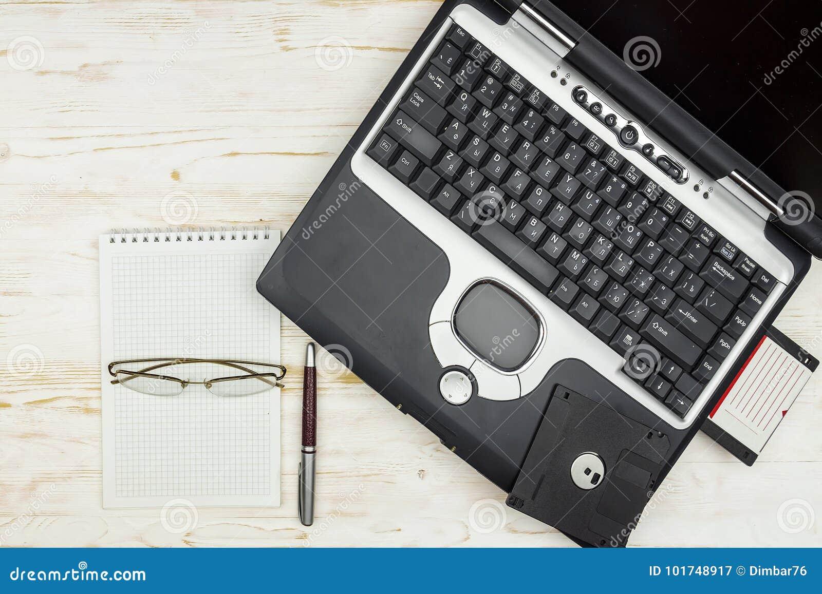 Stary laptop z opadającymi dyskami, notatnikiem, szkłami i piórem na a,