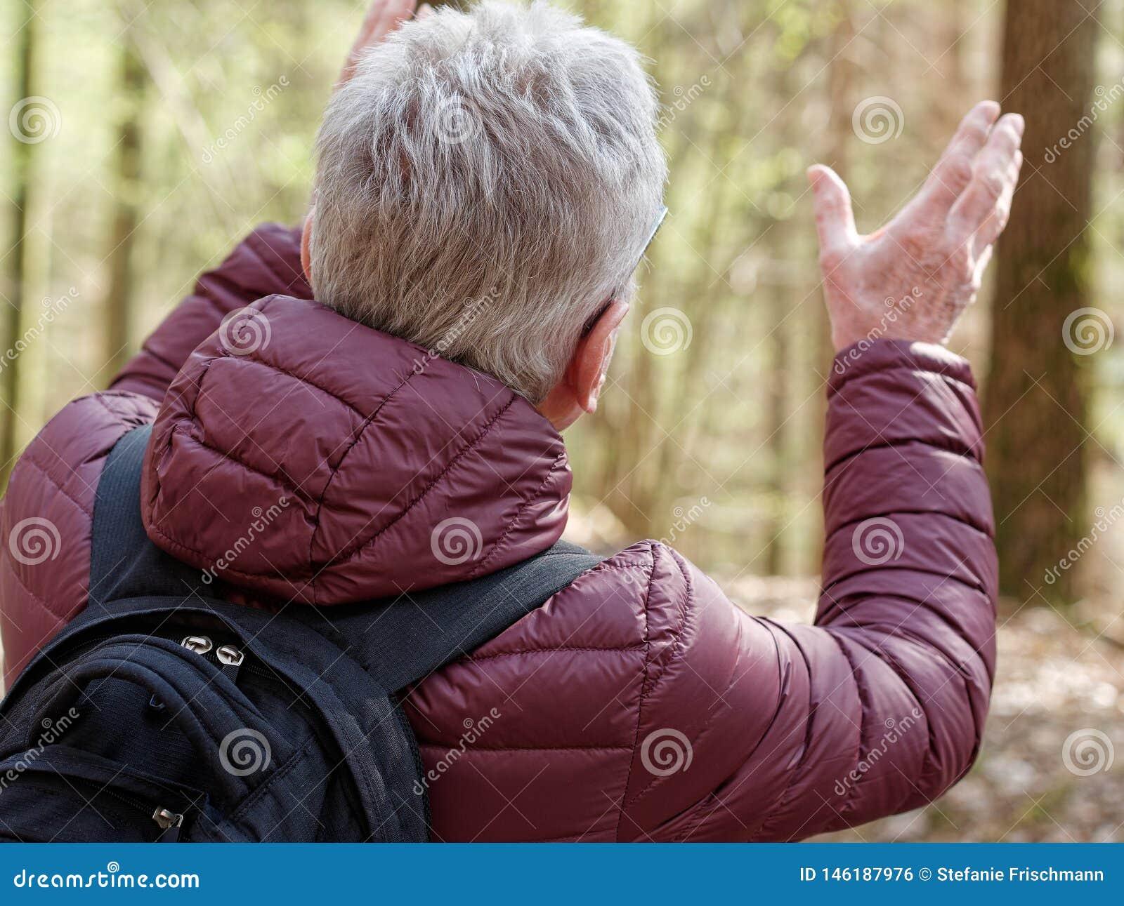 Stary mężczyzna gestykuluje z jego rękami