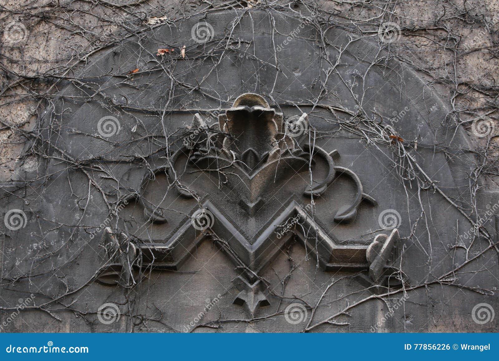 Stary monogram M przerastający z pięcie roślinami w Berlin, Niemcy