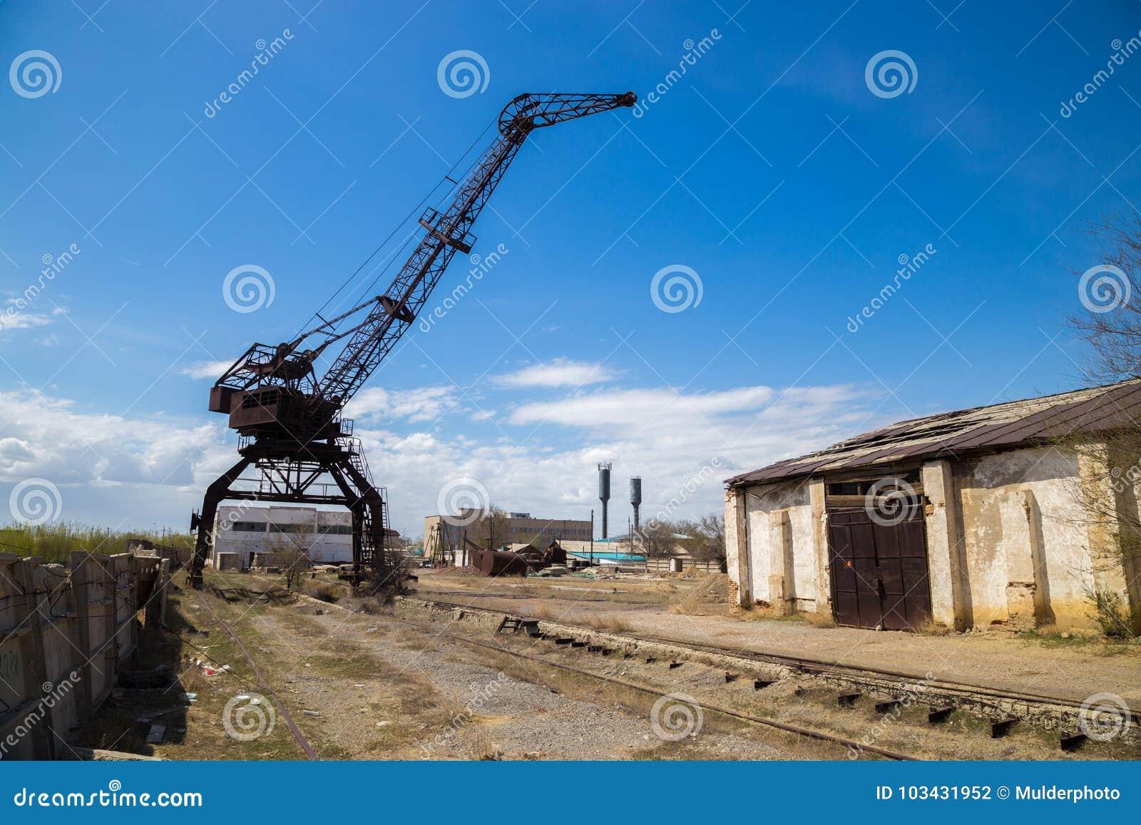 Stary ośniedziały żuraw w zaniechanym przemysłowym terenie