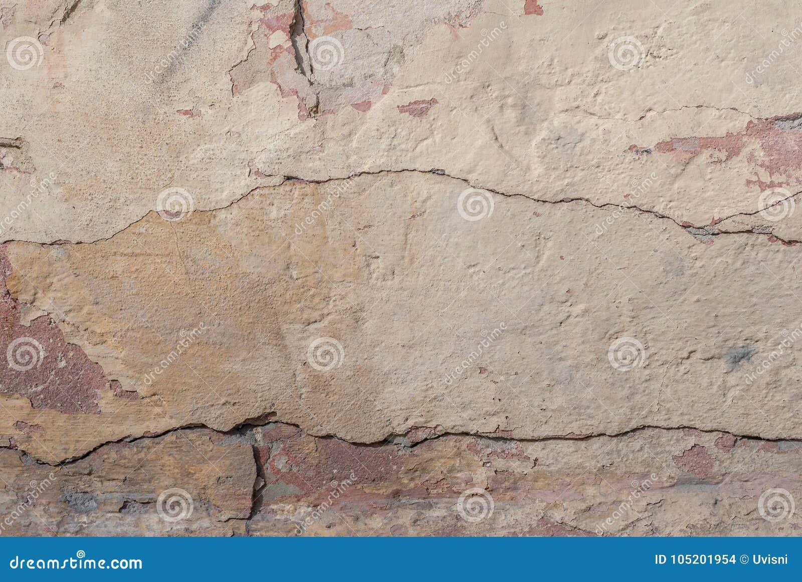 Stary odłupany tynk na betonowej ścianie, szczerbiąca się farba, beżowa tekstura, tło