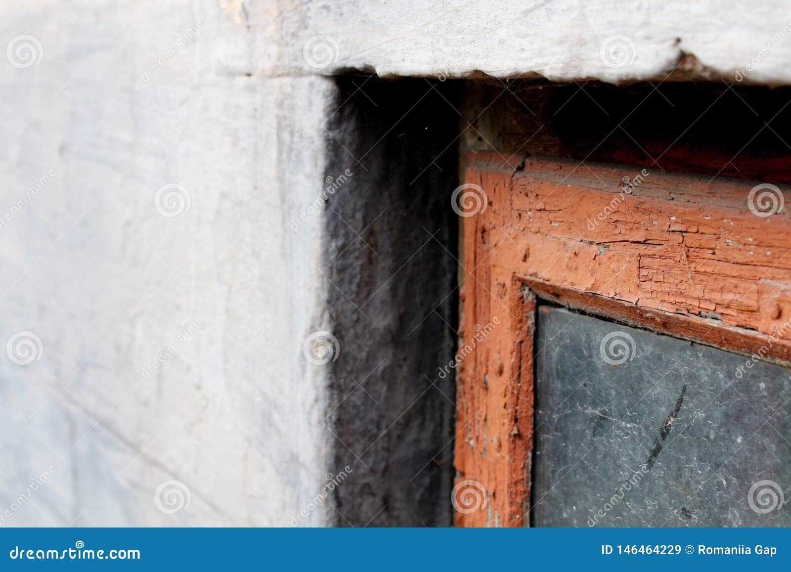 Stary okno w czerwonej ramie z brudnym szkłem na szarej fasadzie Widok jest zamkni?ty