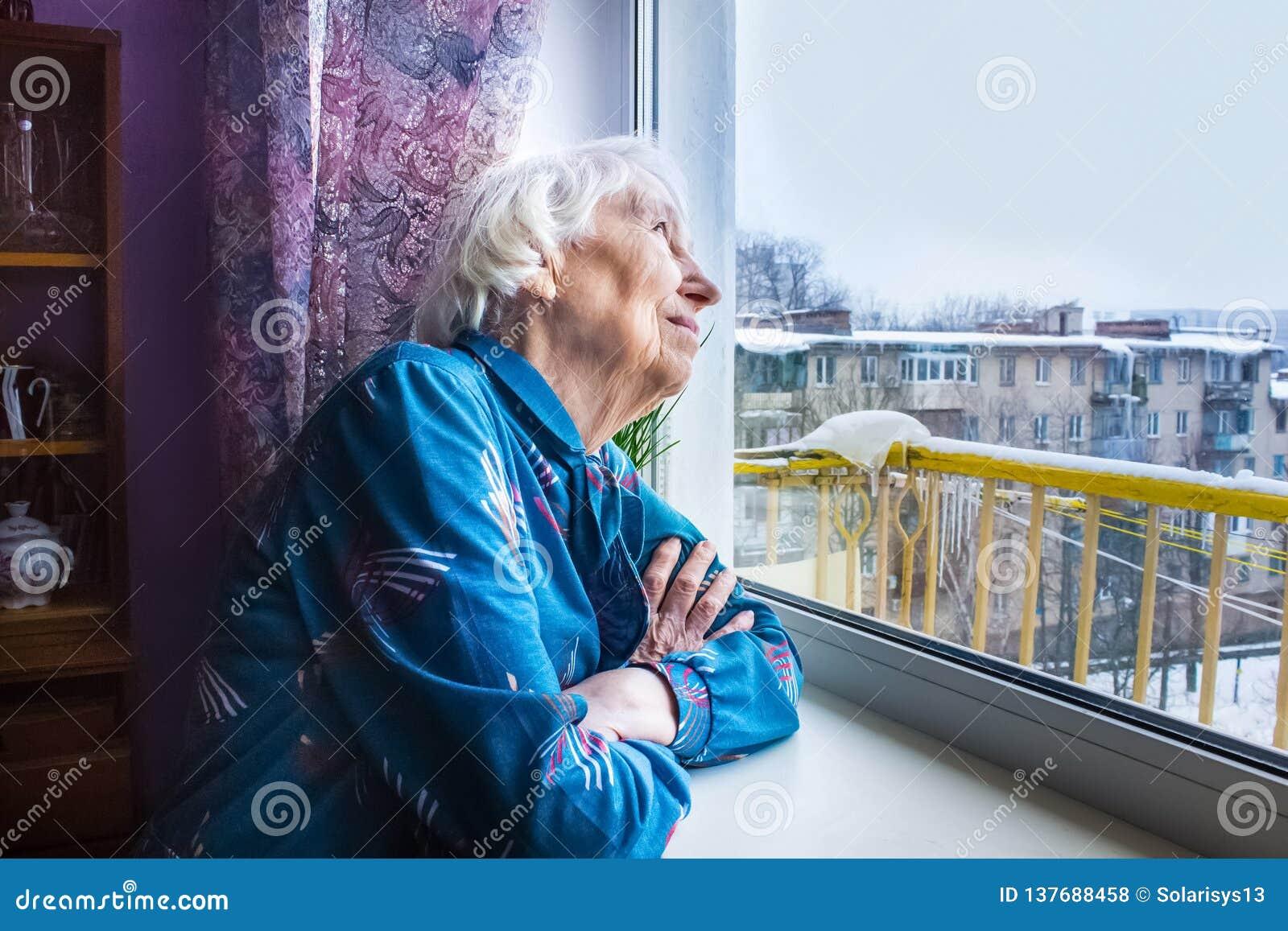 Kobieta Patrzeje Przez Okno, Relaksuje Zdjęcie Stock