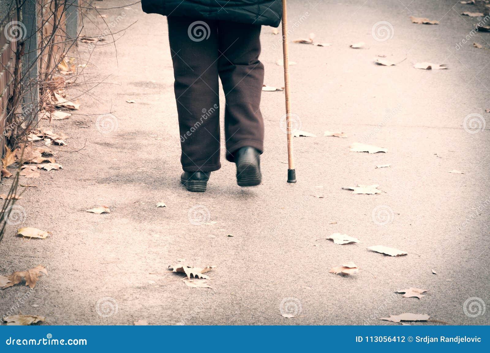 Stary przygnębiony kobieta spacer samotnie zestrzela ulicę lub osamotnionym i przegranym od plecy z chodzącego kija, trzciny uczu