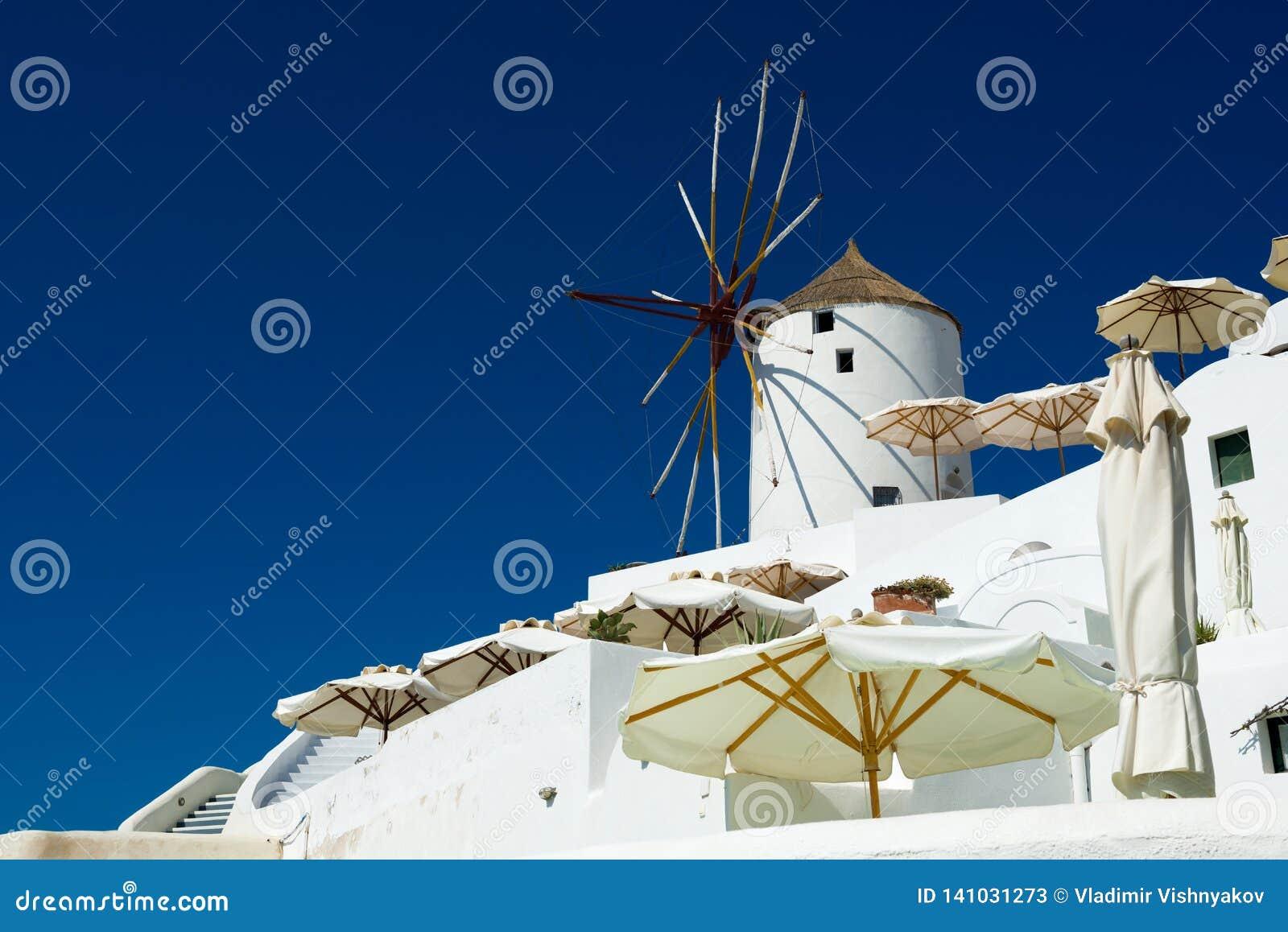 Stary wiatraczek w Oia na słonecznym dniu, Santorini, Grecja
