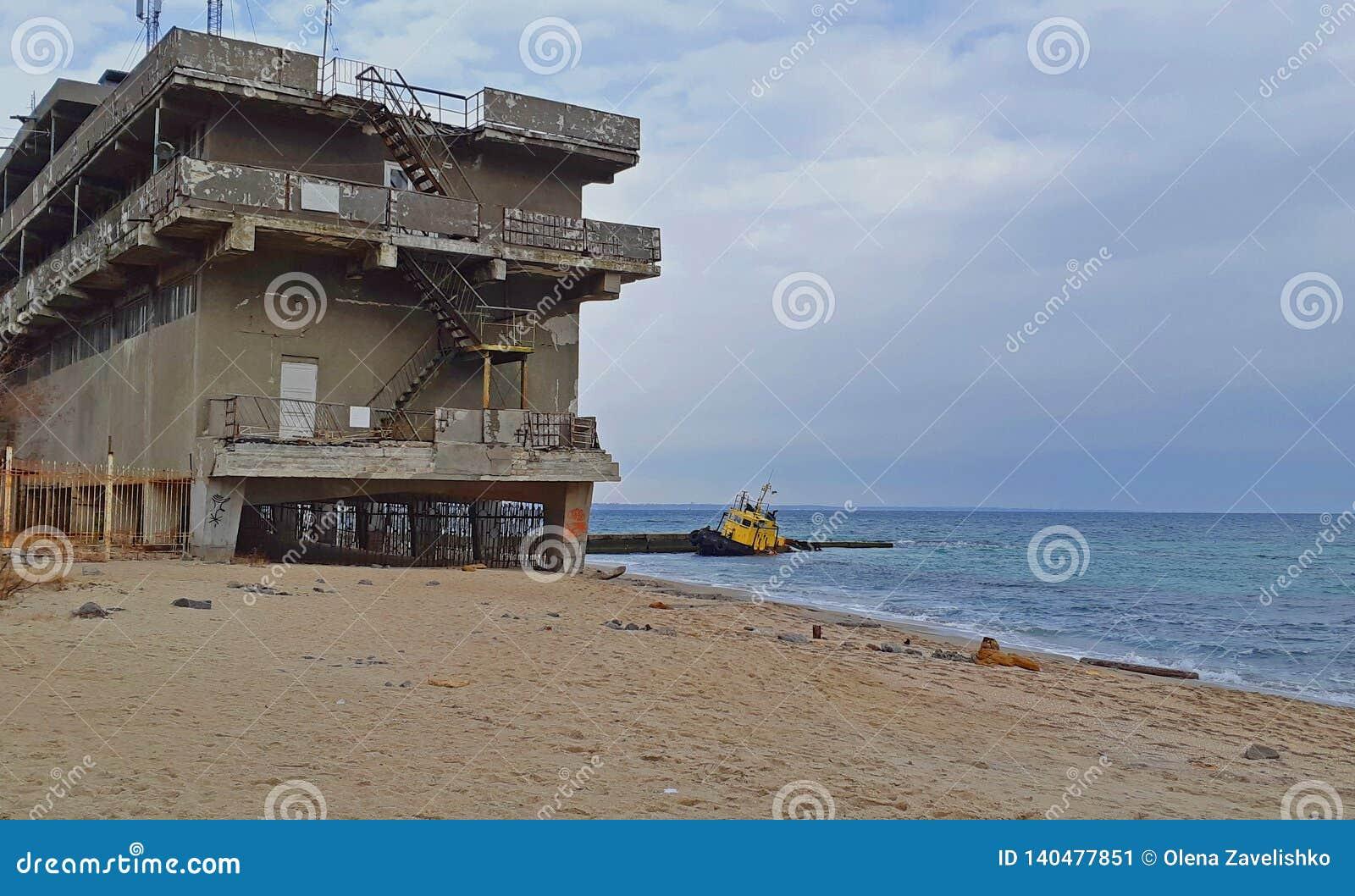 Stary zalewający holować statek i zaniechany budynek blisko brzeg Dramatyczny widok zalewająca łódź blisko brzeg