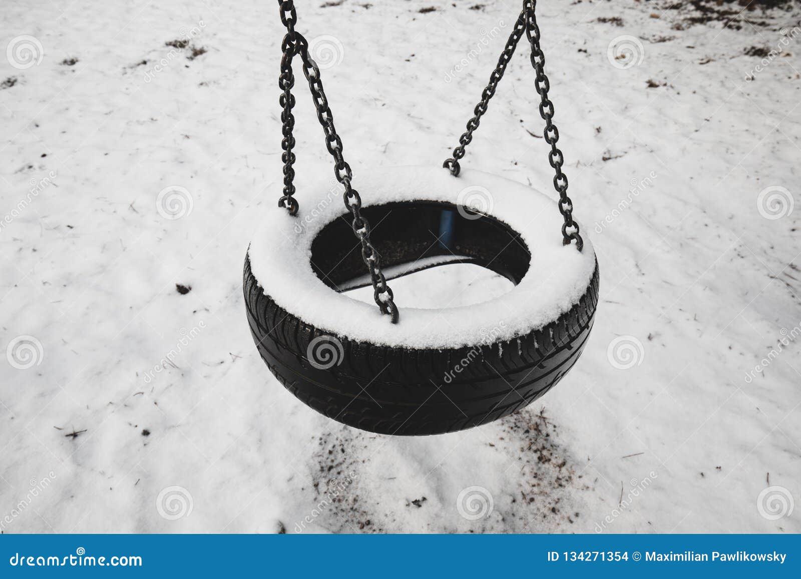 Stary zaniechany set opon huśtawki zakrywać śniegiem przeciw zima lasu krajobrazu tłu Dzieciństwo wspominek pojęcie