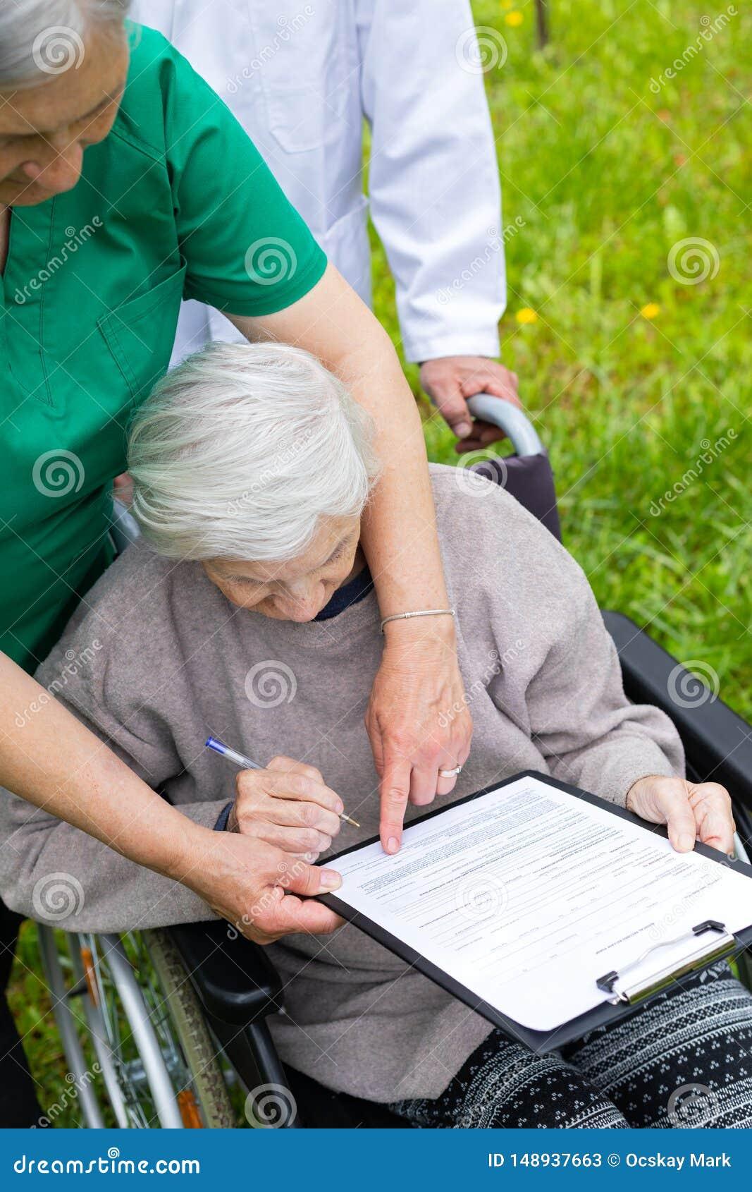 Starzej?ca si? kobieta w w?zku inwalidzkim z medyczn? pomoc?