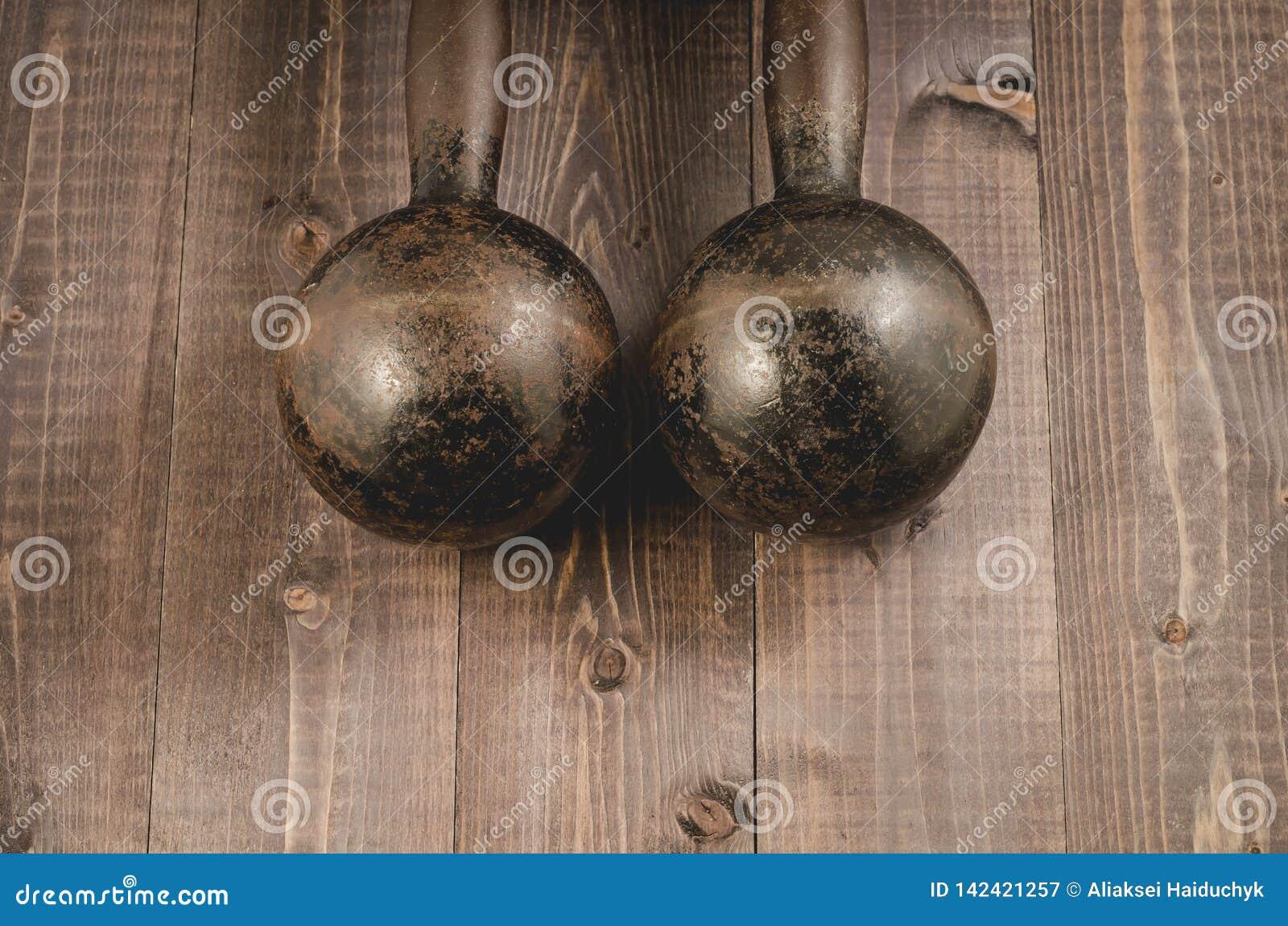 Starzy żelazni dumbbells/starzy żelazni dumbbells na ciemnym drewnianym tle Odgórny widok