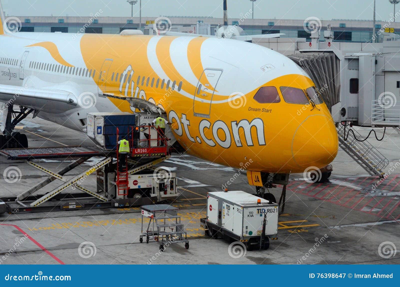 Stationärt Scoot flygbolagflygplanet som servas på Changi flygplatsgrov asfaltbeläggning Singapore