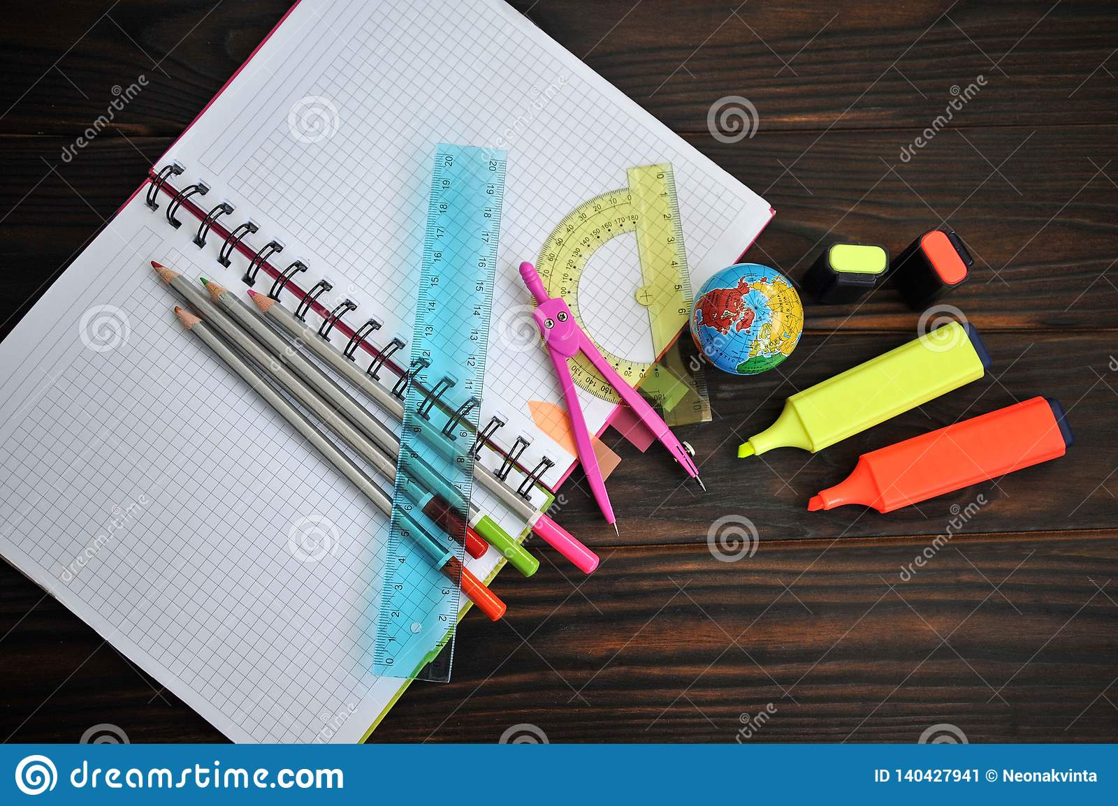 Stationery scattered on a notebook lying on a dark wooden table,