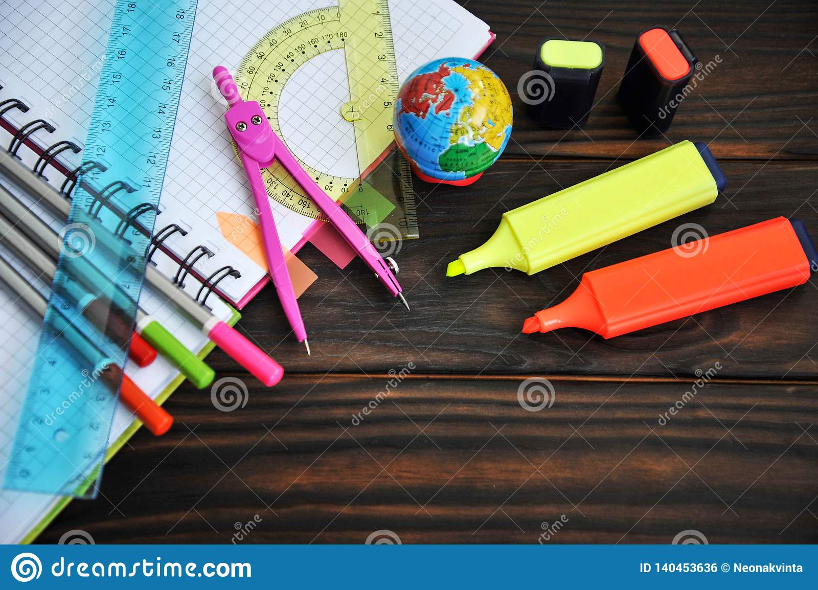 Stationery scattered on a notebook lying on a wooden table