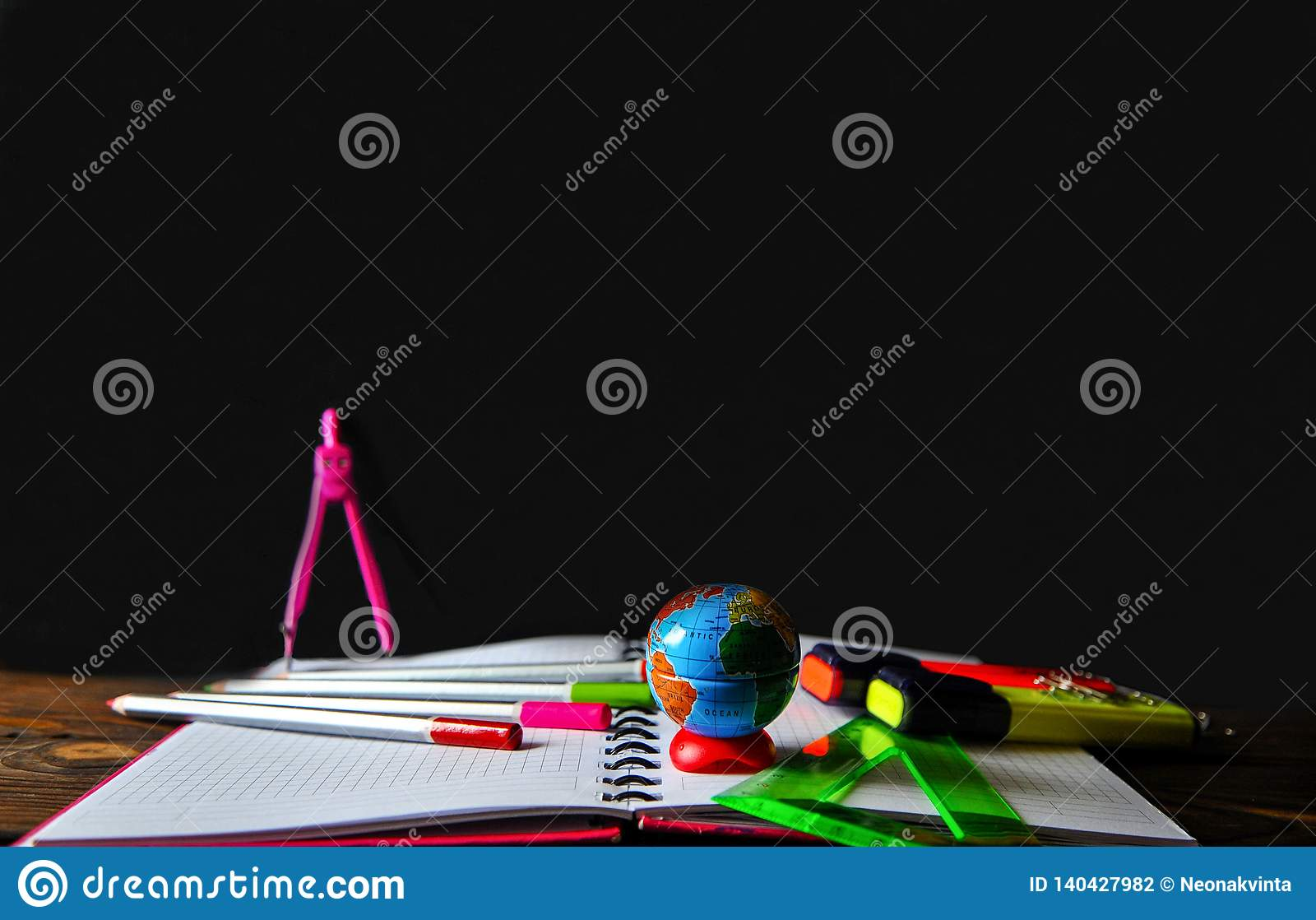 Stationery scattered on a notebook lying on a wooden table on the background of a board