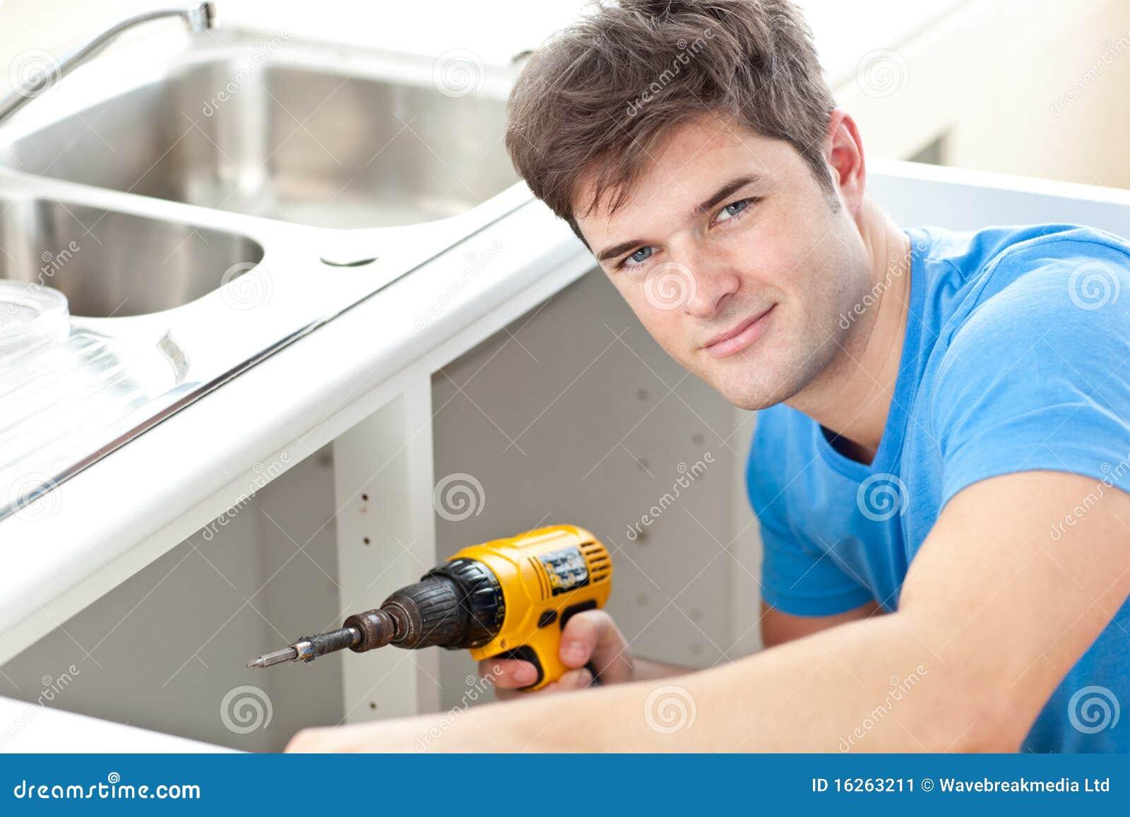Stattlicher Mann mit einem Bohrgerät, das eine Küchewanne repariert