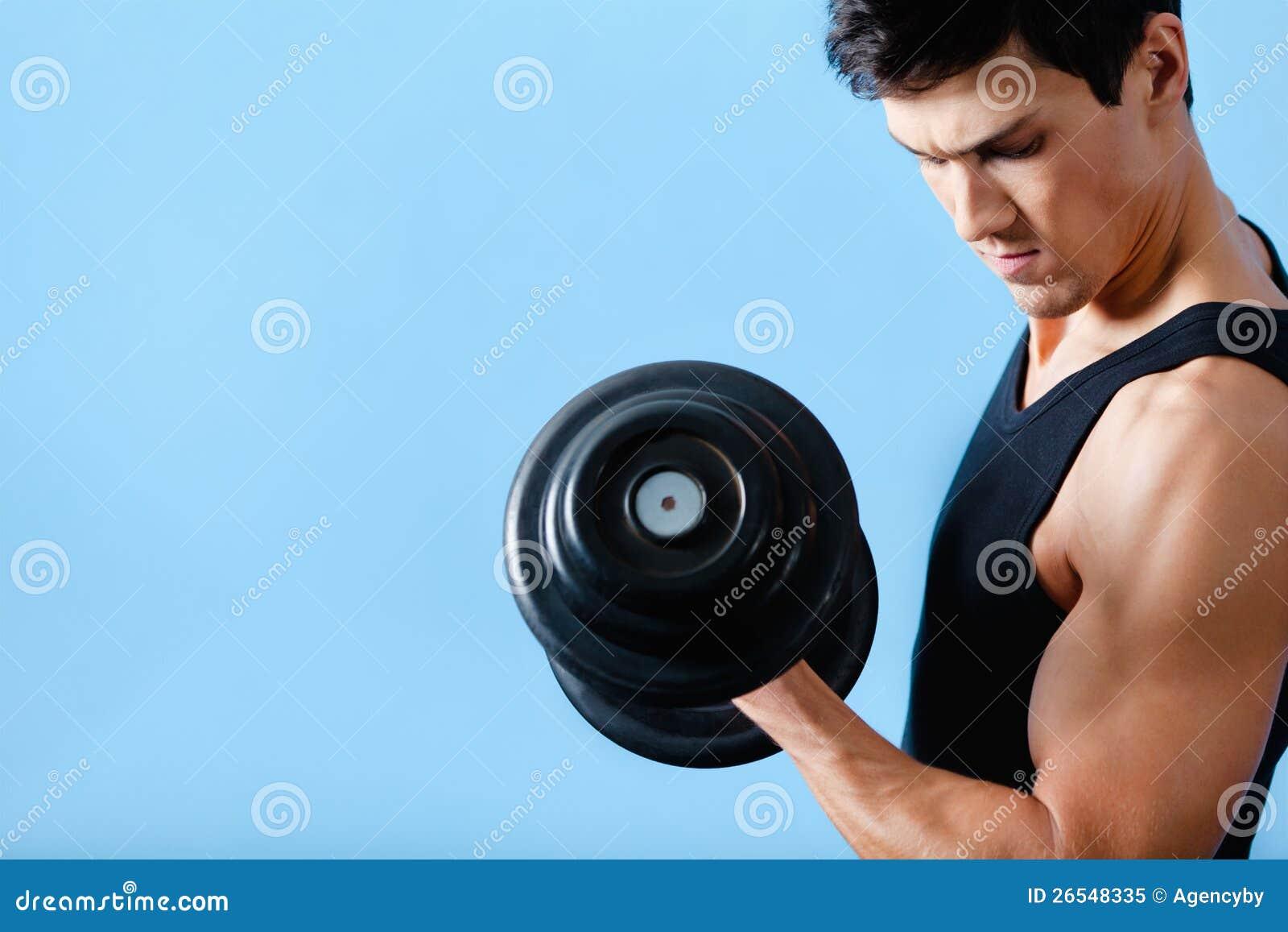 Stattlicher muskulöser Mann verwendet seinen Dumbbell