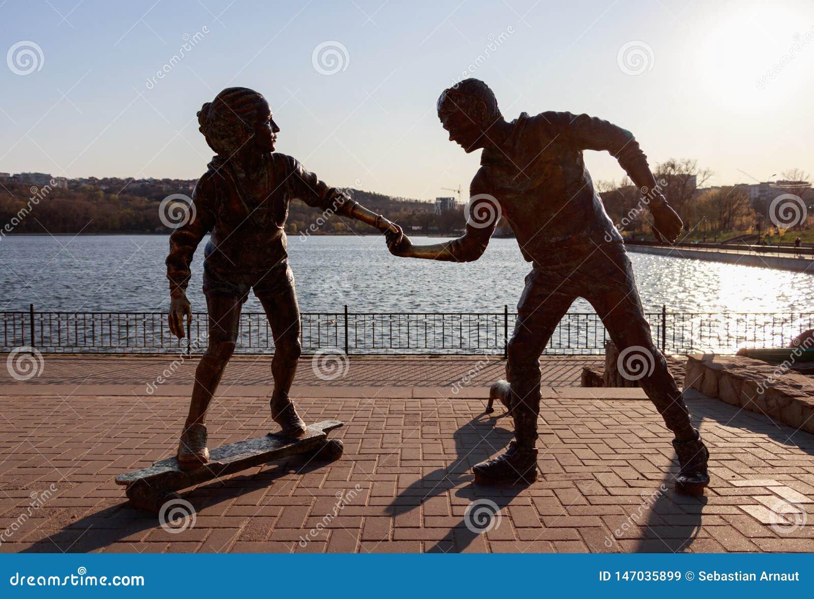 Statua con un ragazzo e una ragazza che tengono la sua mano