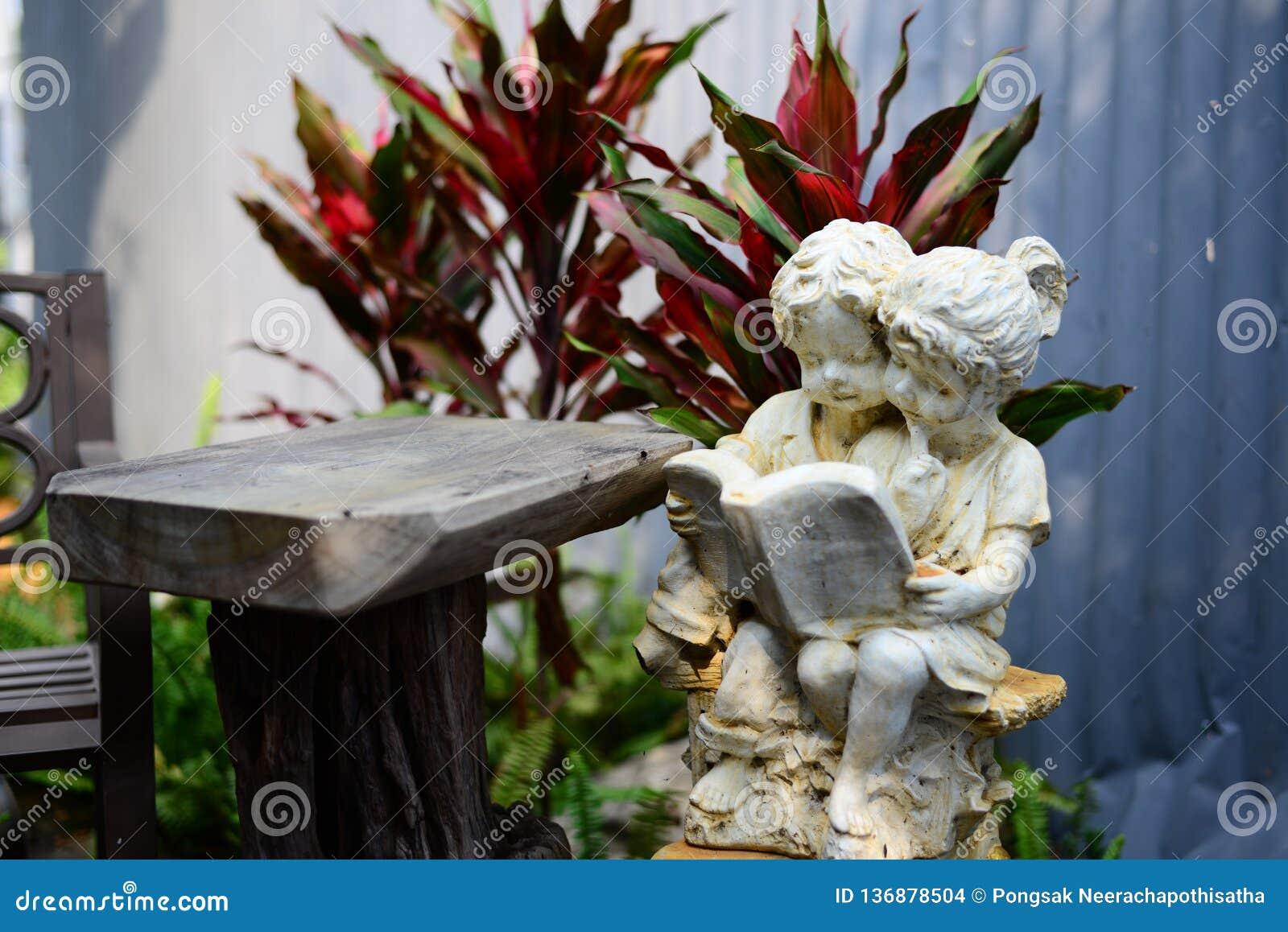 Statua dziewczyna i chłopiec czyta książkę w ogródzie