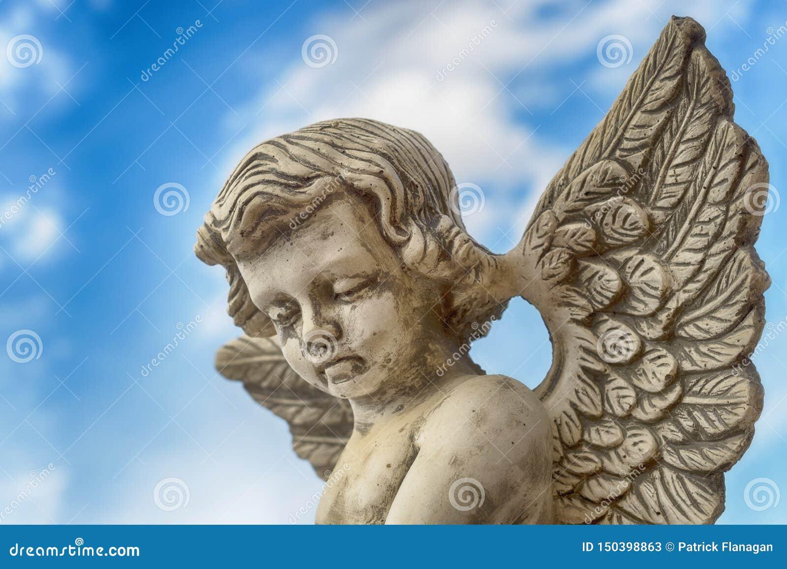 Statua popielaty kamienny anioł przeciw niebieskiemu niebu