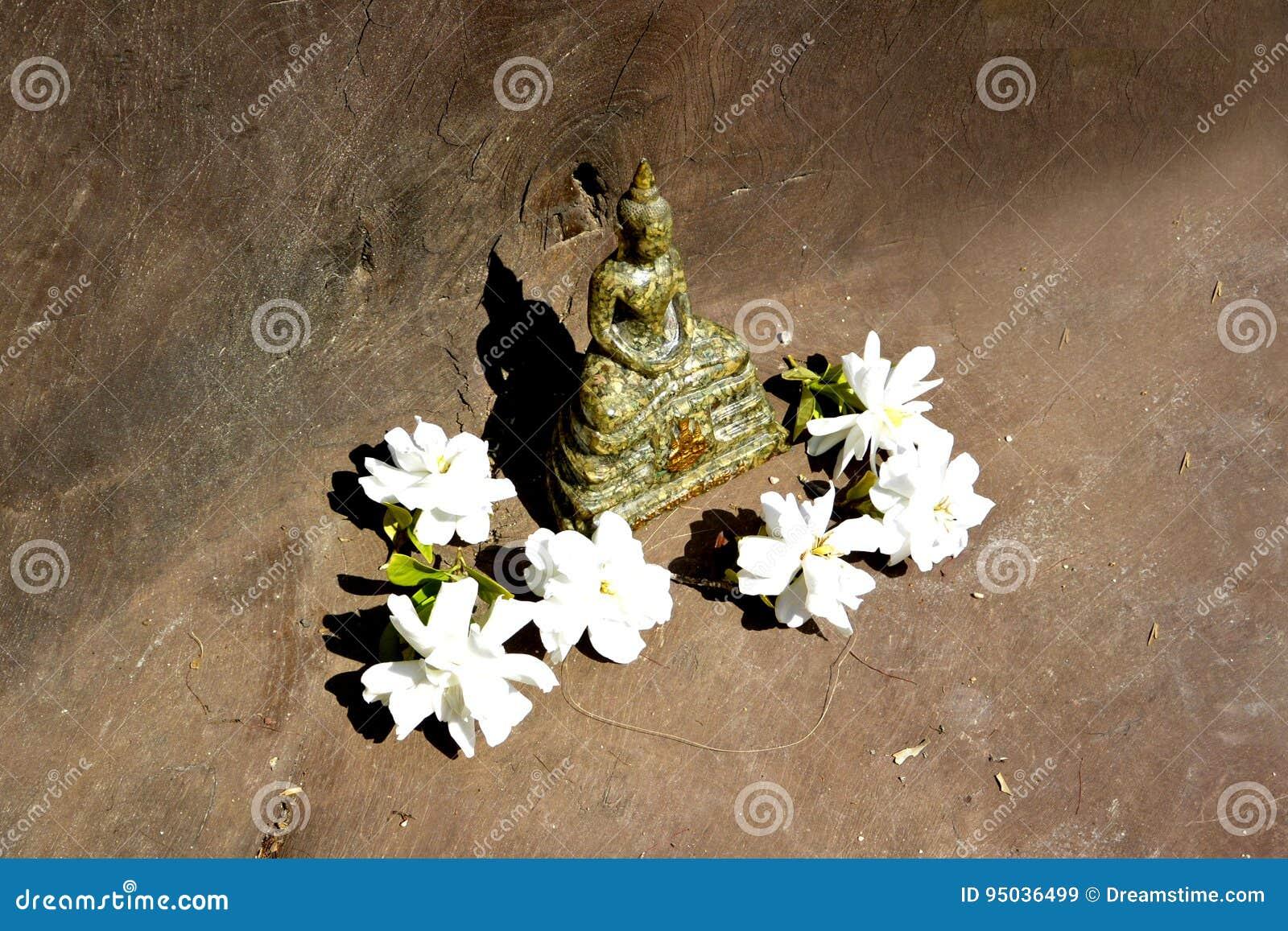Statua Tajlandzki Buddha w medytaci pozie z białymi kwiatami