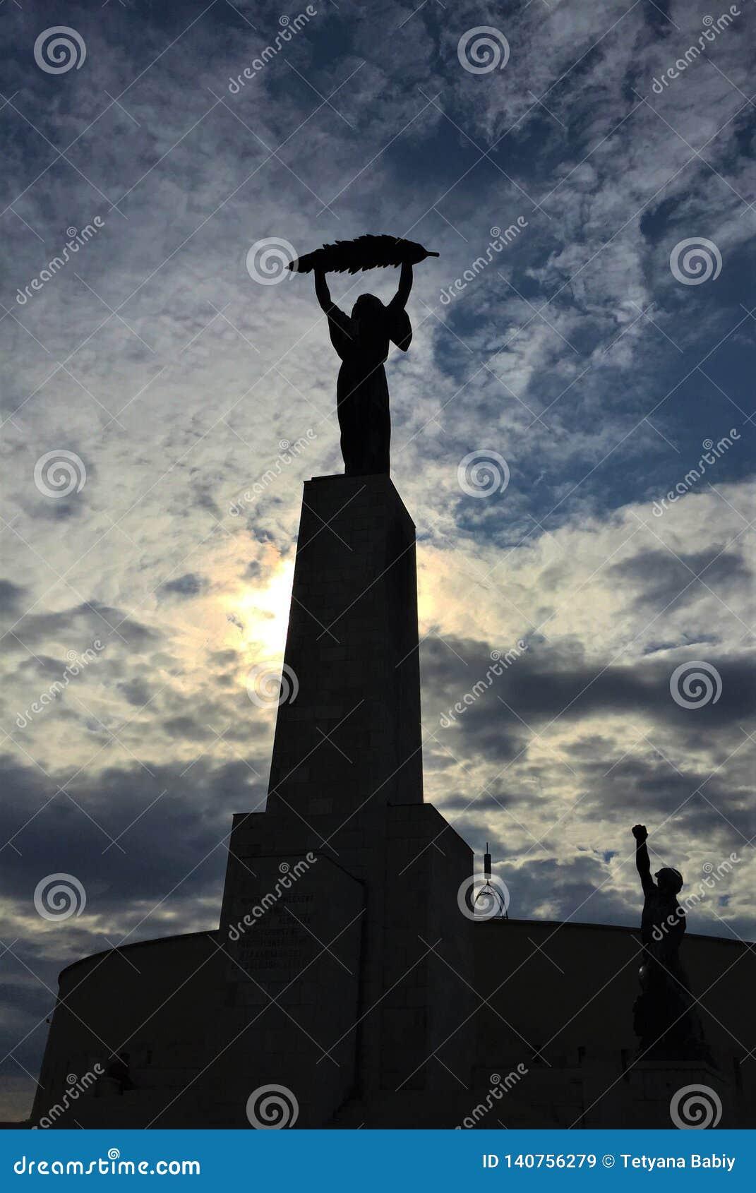 Statua Wolności - brązowa kobieta trzyma palmowego frond