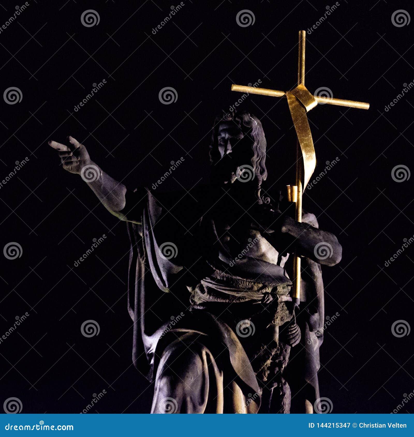 Statue of a bridge saint holding a large golden cross at night
