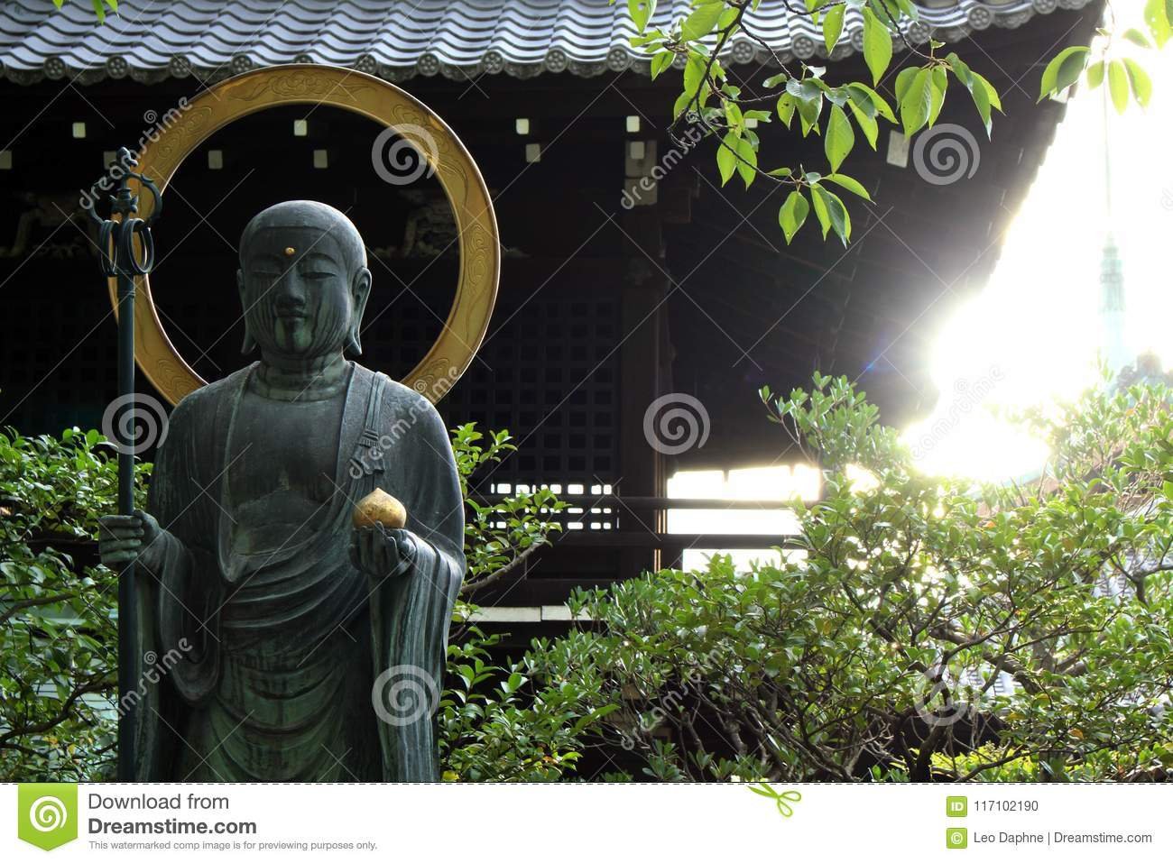 The statue of buddha holding a lotus flower while the sun s stock download the statue of buddha holding a lotus flower while the sun s stock izmirmasajfo