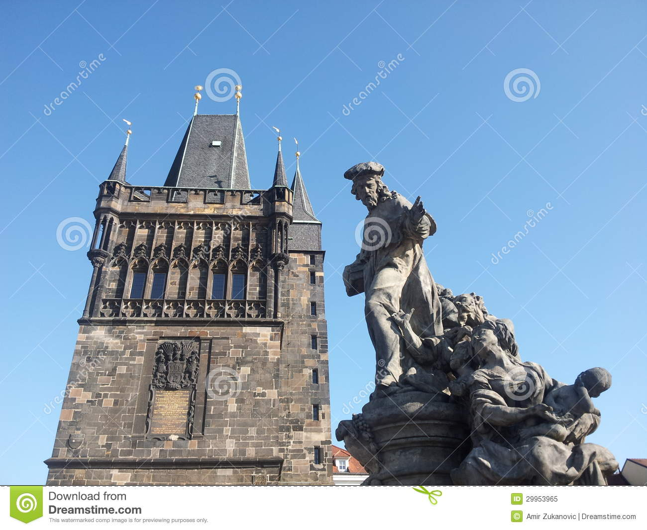 Statue on Charles bridge with tower in background