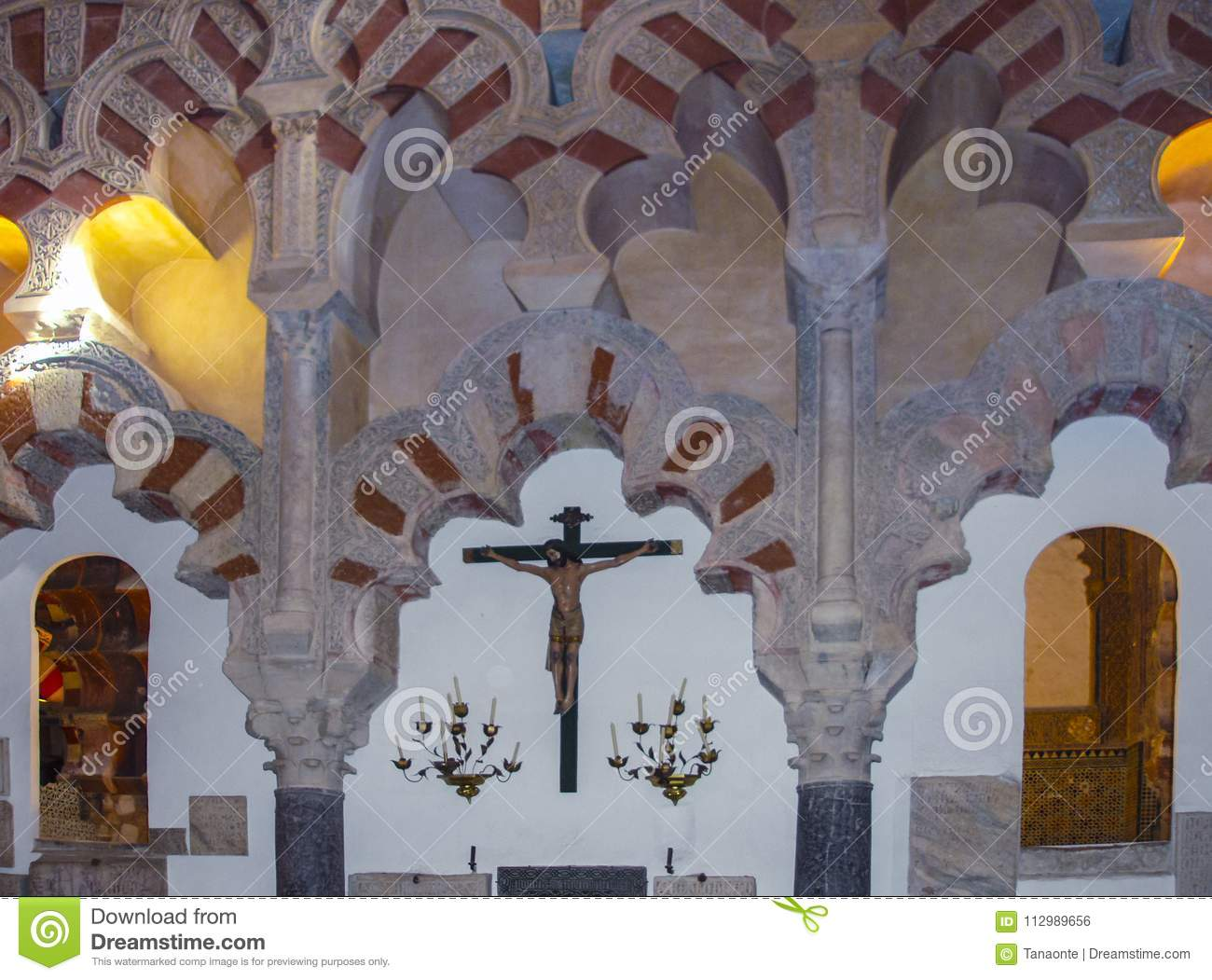 Statue of the crucifixion and moorish arch in Cordoba mosque