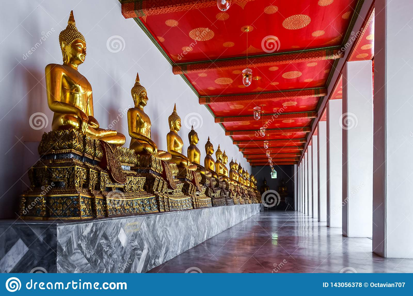 Statue dorate multiple di Buddha in tempio in Tailandia