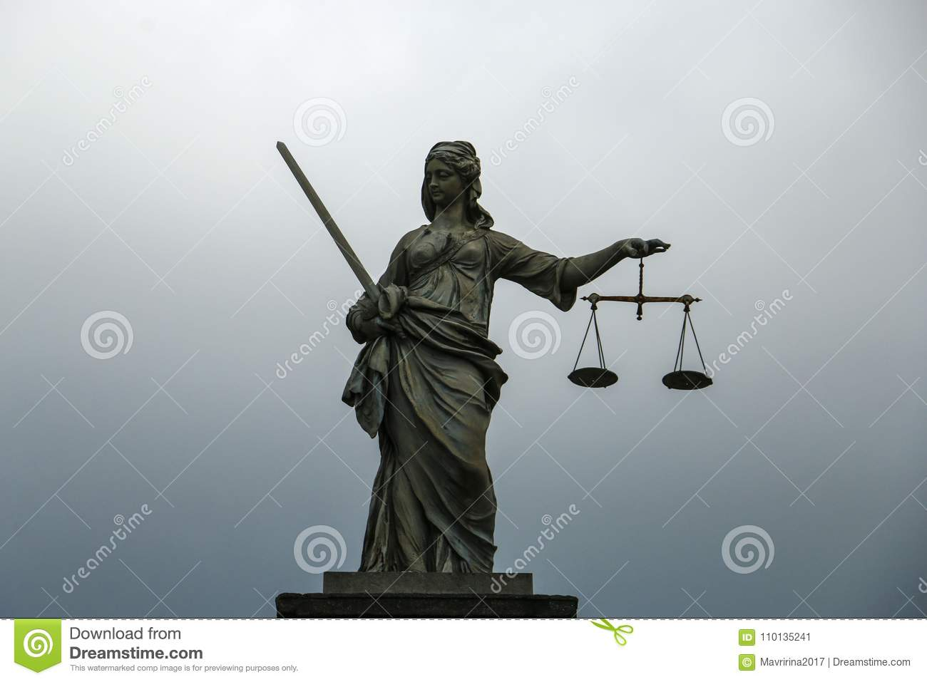 Statue of Themis, goddess of justice on a gray-blue background