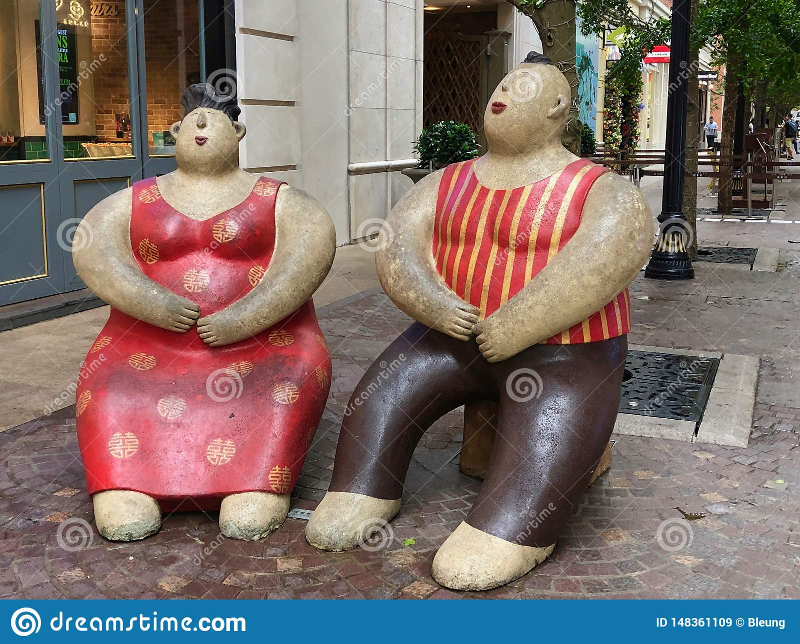 Statues of a couple enjoying sitting outdoor in Hong Kong