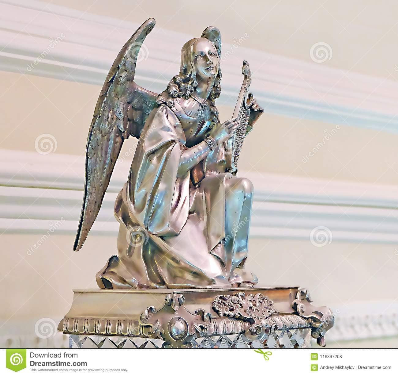 Statuette of an angel and other retro things are standing on a wooden table.
