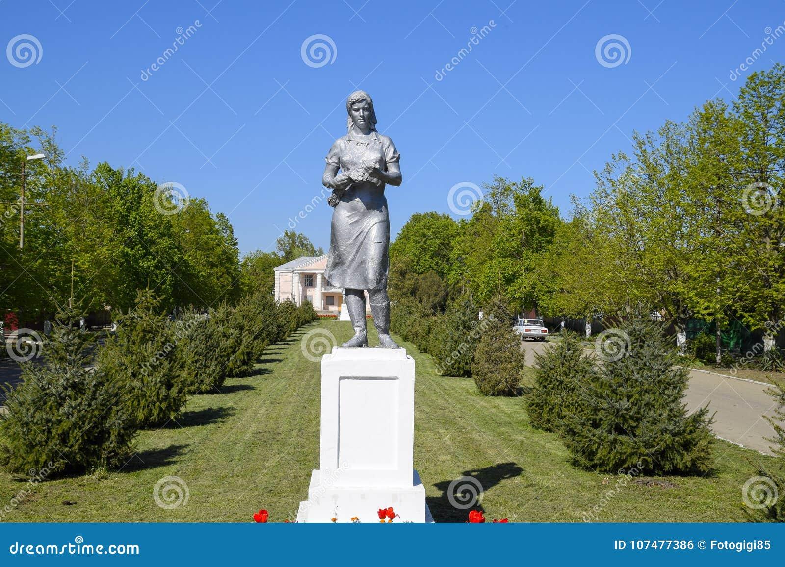 Staty av en kollektiv bonde på en sockel Legaten av den sovjetiska eran En rabatt med tulpan och barnträd in
